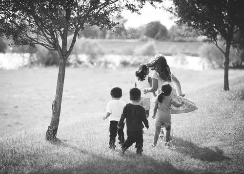 Grayscale Photo of Five Children Near Tree