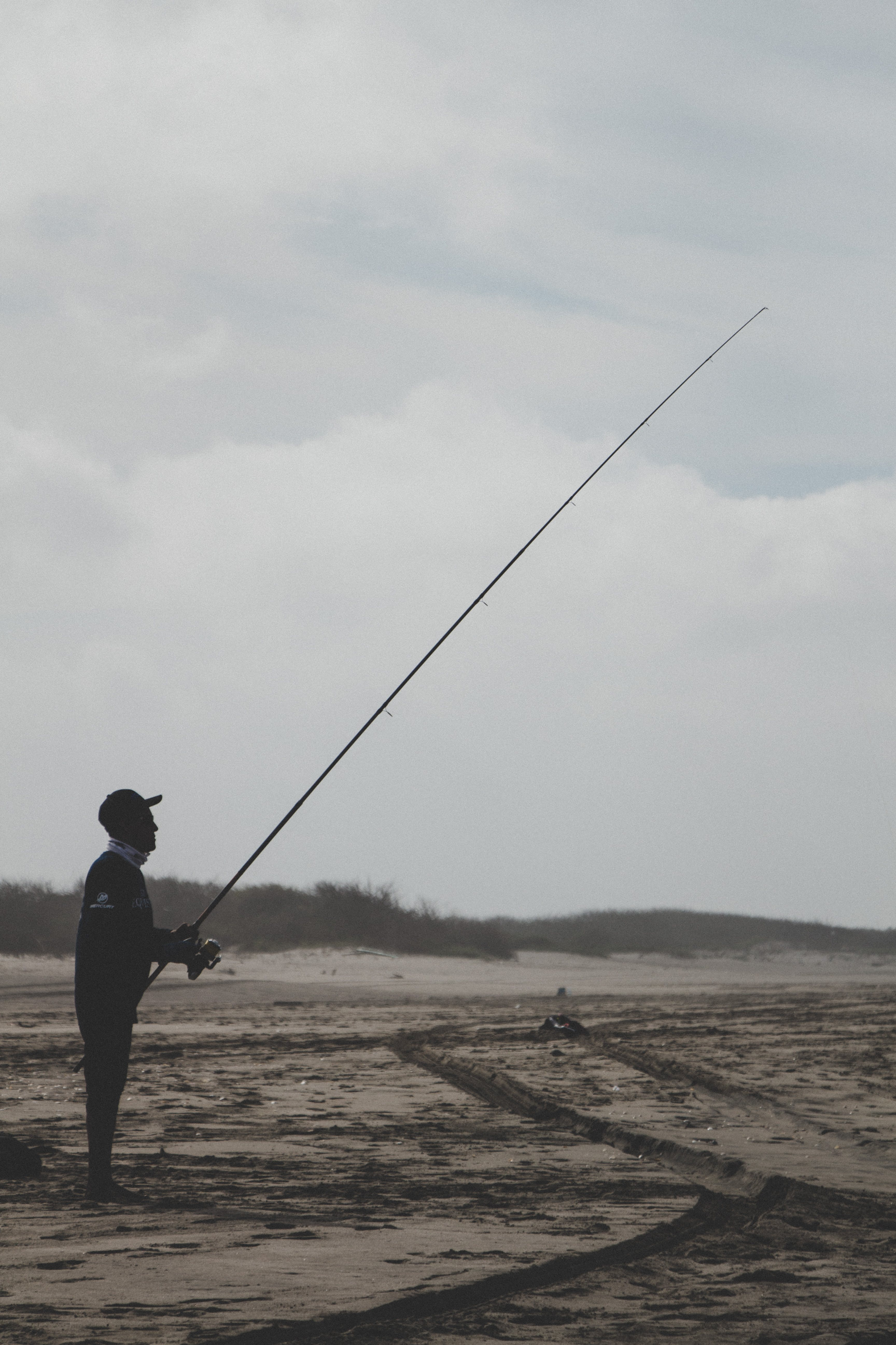 Man Standing Holding a Fishing Rod