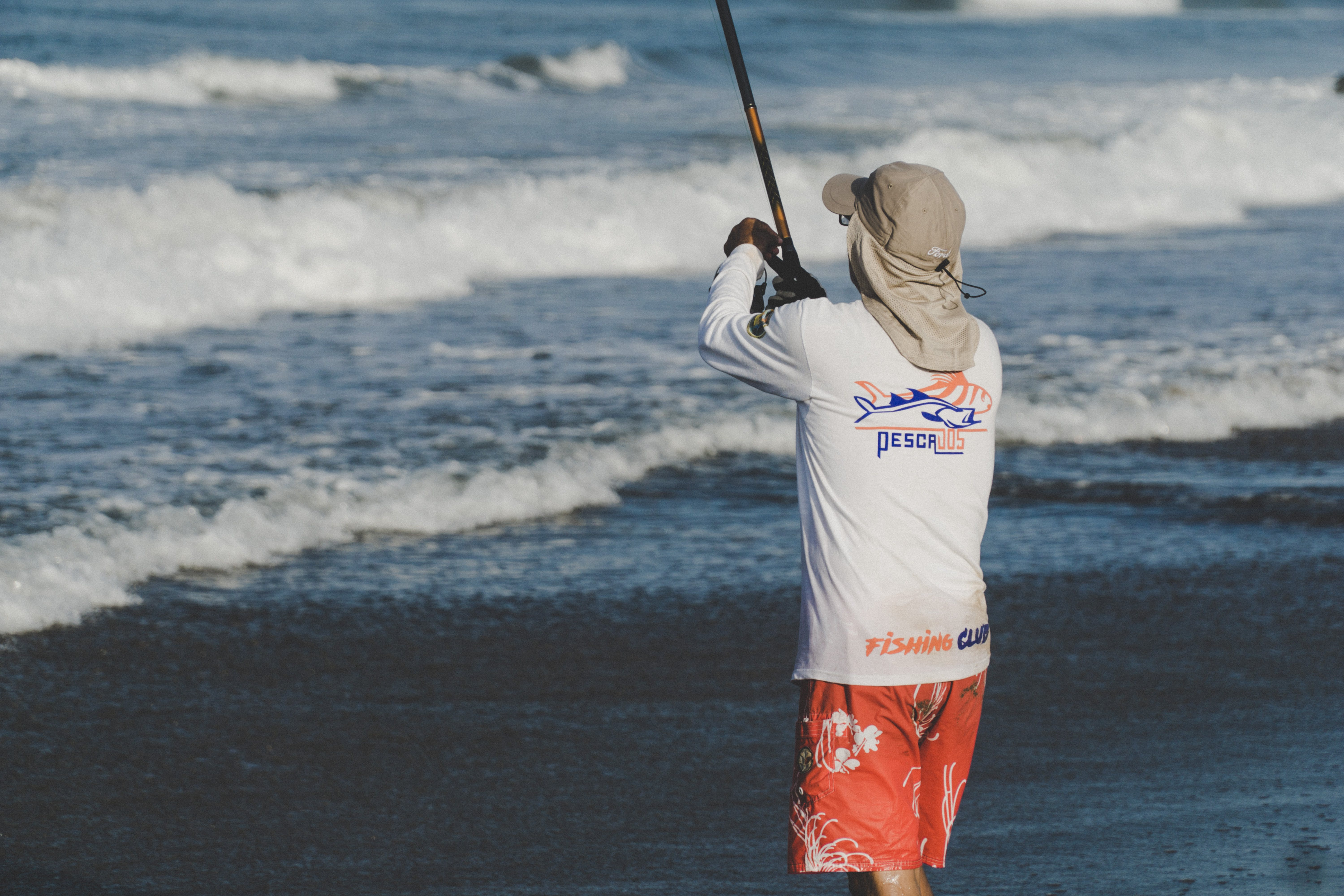 Person Holding Fishing Rod on Beach