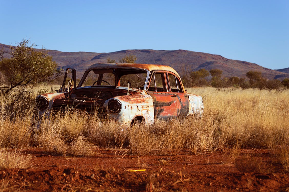 Photo of Corroded Vintage White and Red Sedan on Brown Grass