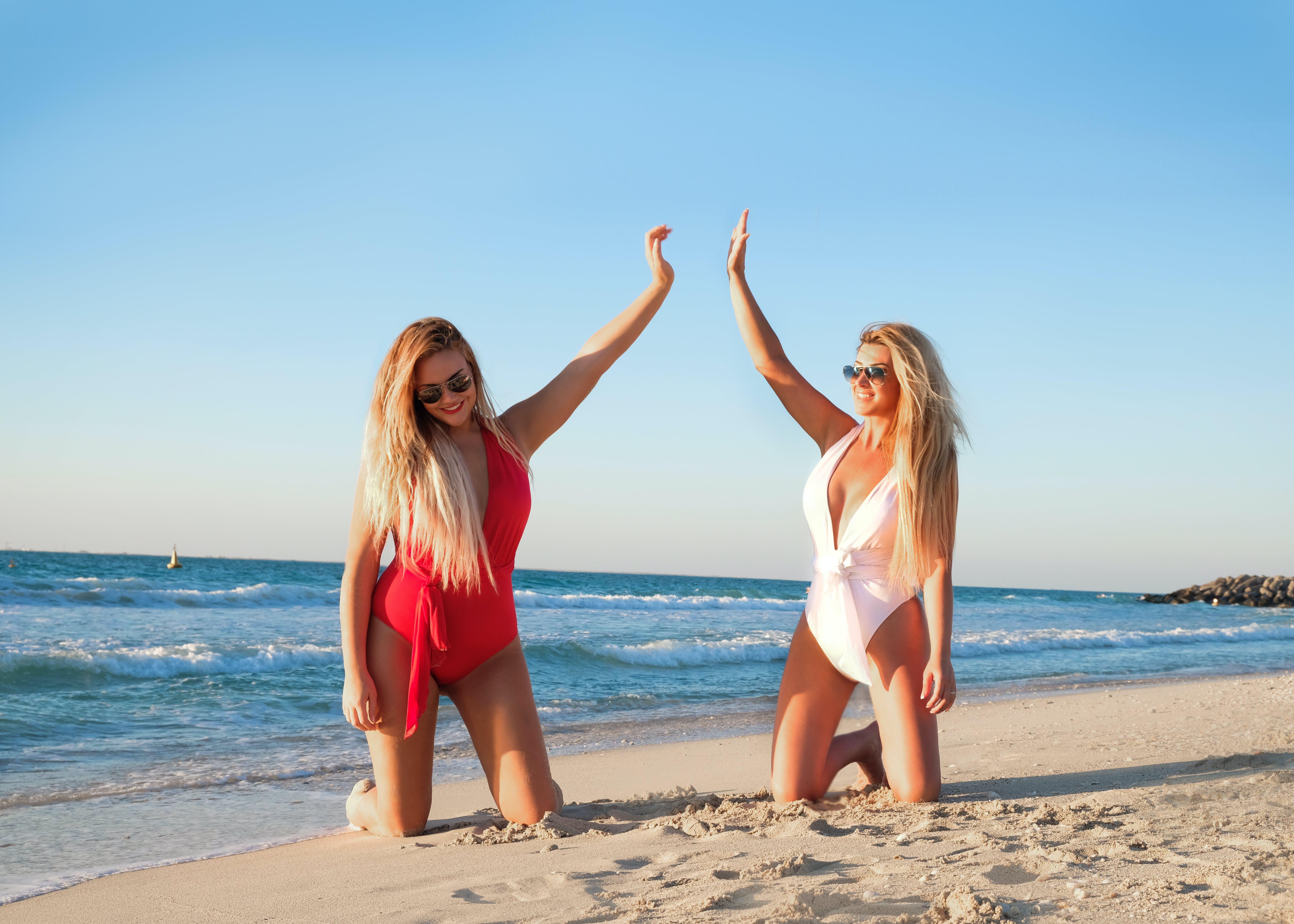 Two Woman Kneeling on White Sand Beach