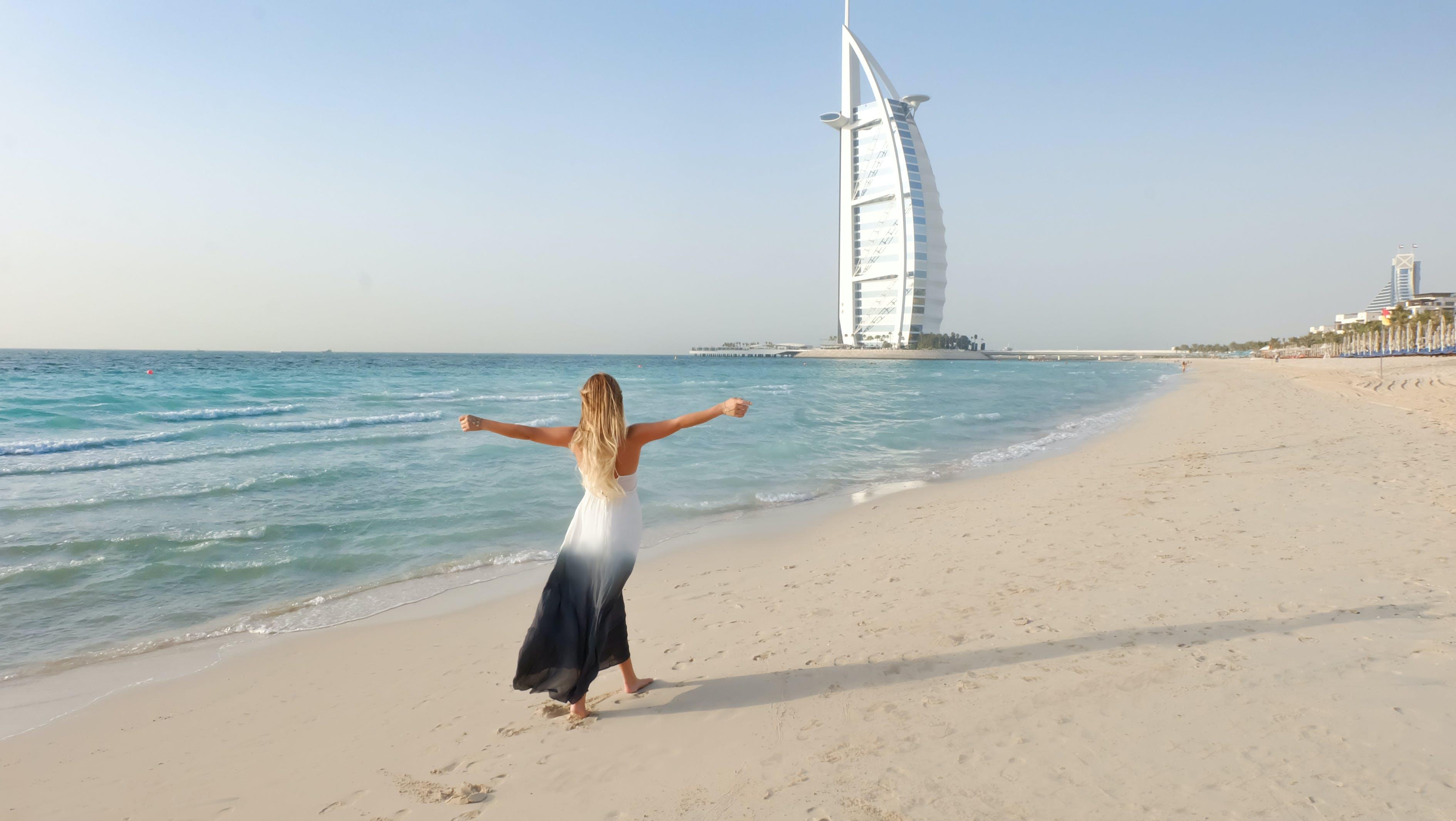 Photography of Woman Walking On Seashore
