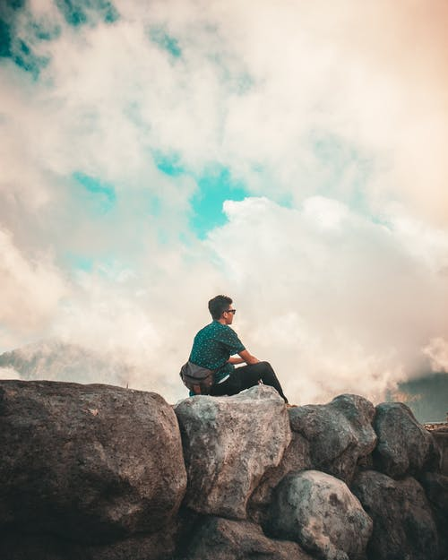 Man in Green Shirt and Black Pants Sitting on Top of Rock Cliff Under White Clouds