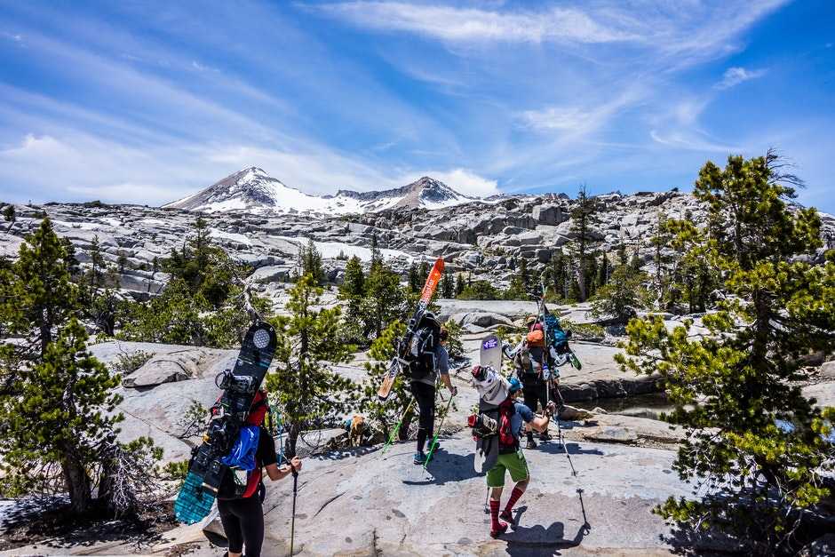 Group of People Hiking With Snowboards Under Blue Cloudy Sky