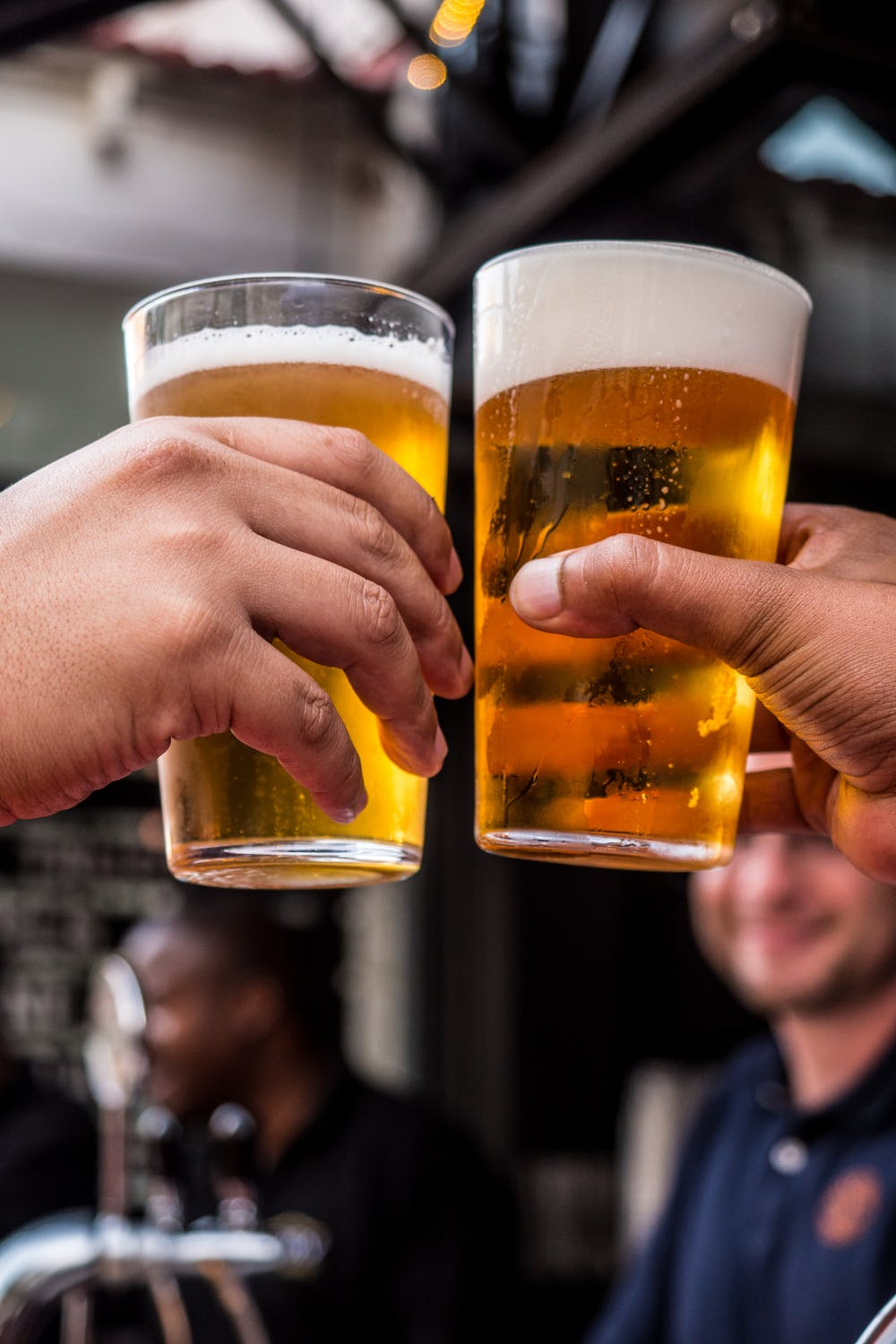 Two persons holding drinking glasses filled with beer. | Photo: Pexels
