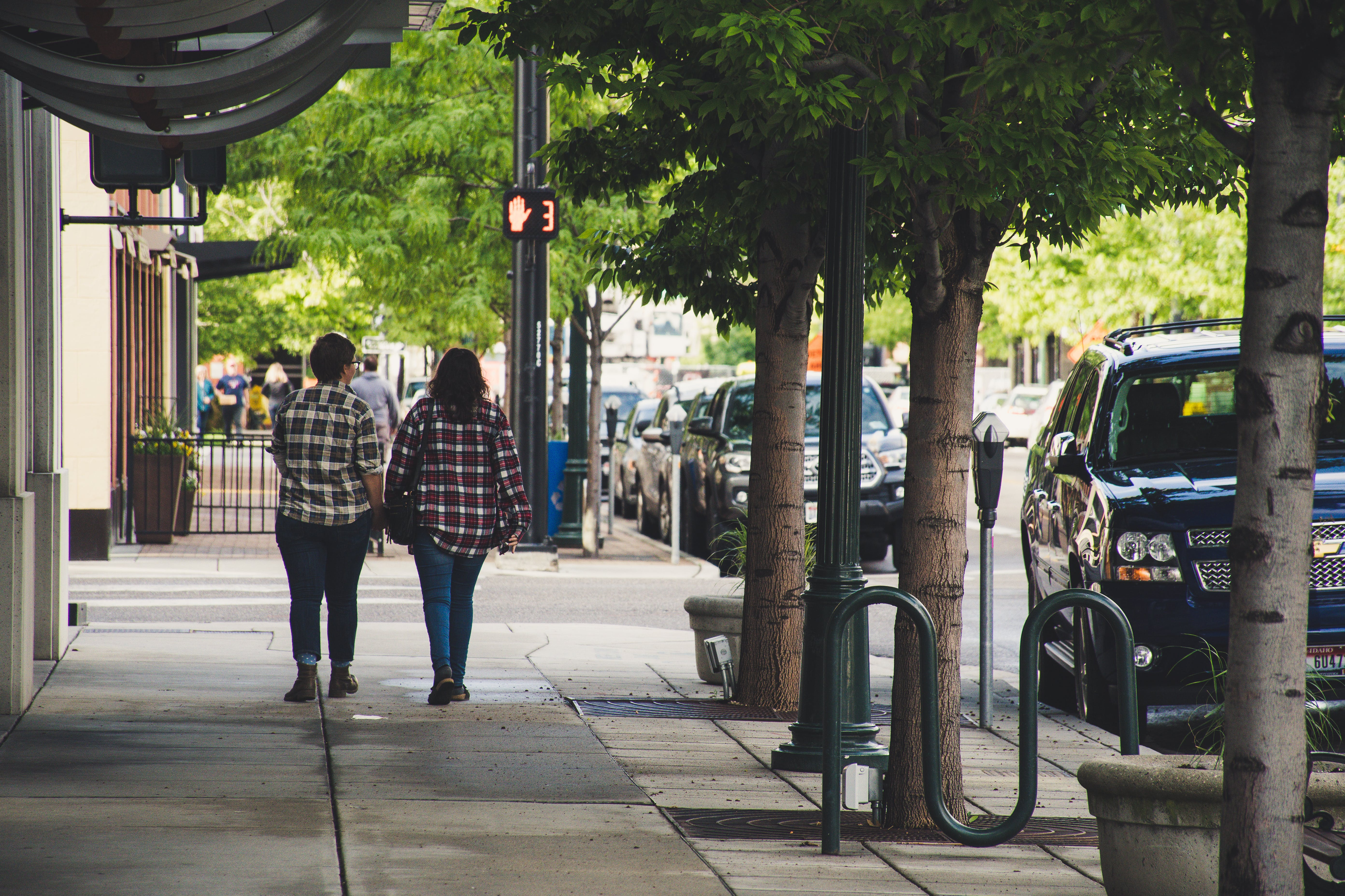 Two Woman in Plaid Sport Shirt Walking on Concrete Pathway Near Street
