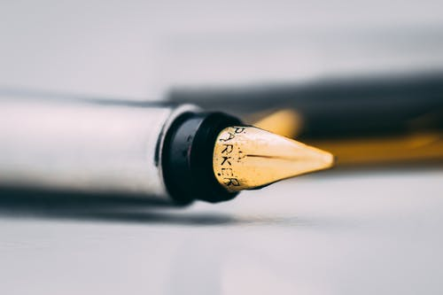 Selective Focus Photography of Fountain Pen on White Surface