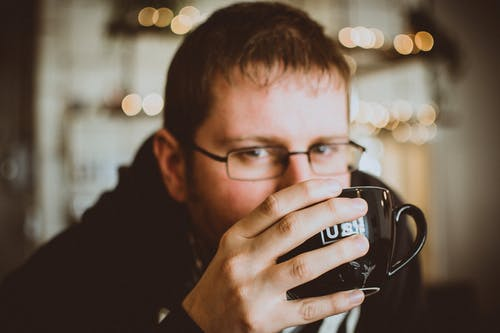 Man in Black Jacket Holding a Mug