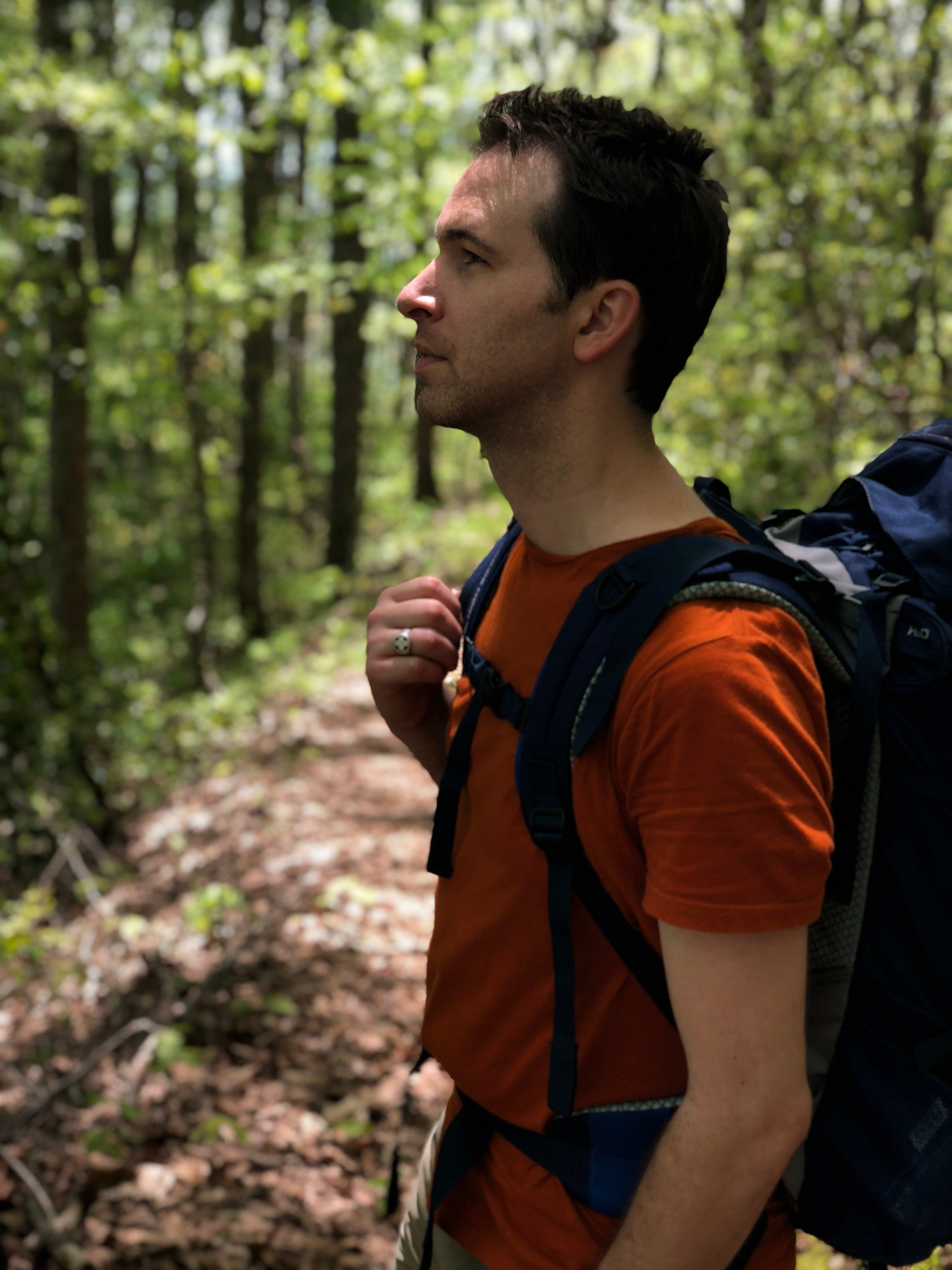 Man in Red Crew-neck Shirt Carrying Blue Hiking Backpack
