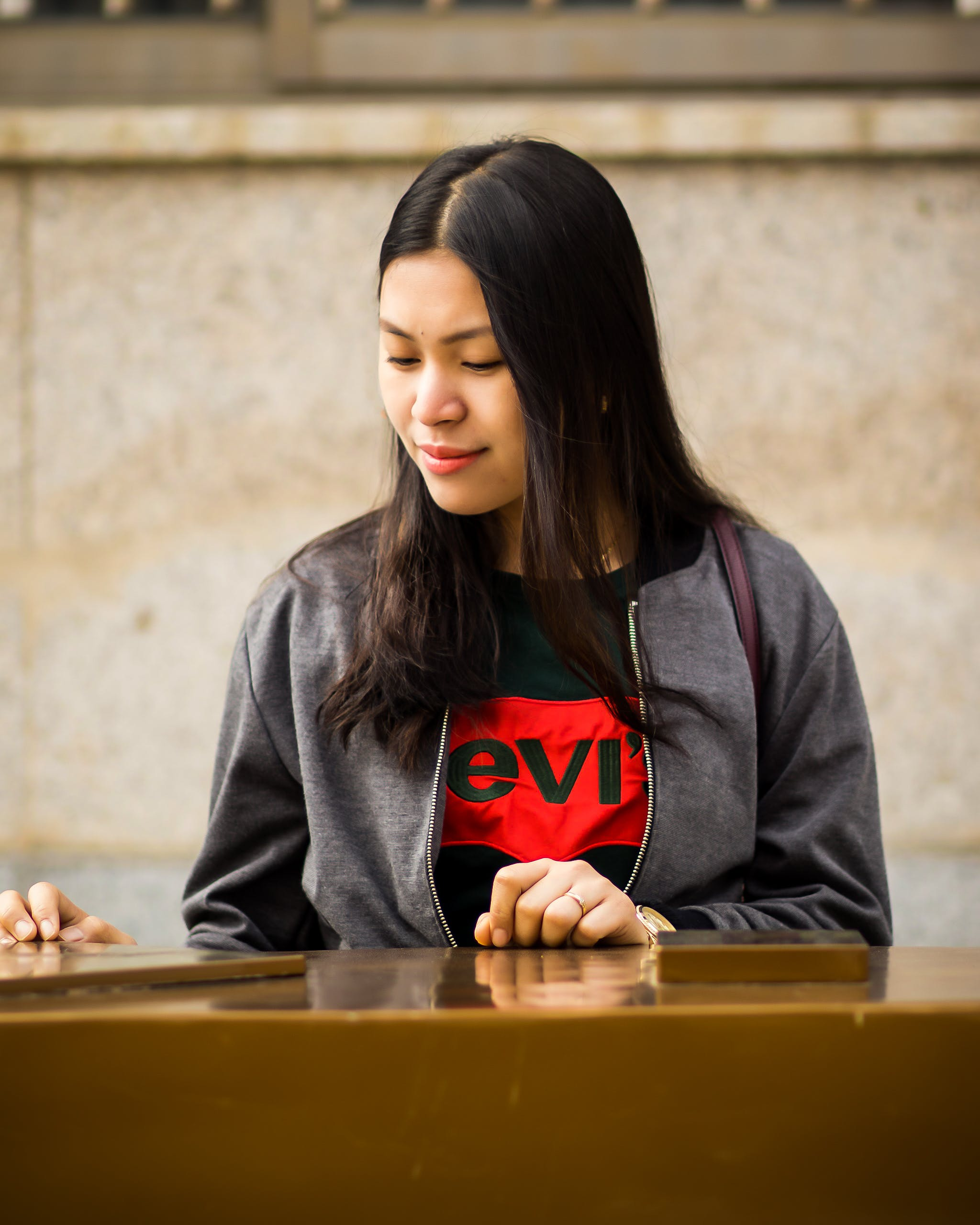 Woman Wearing Black Levis Crew-neck Shirt and Gray Zip-up Jacket