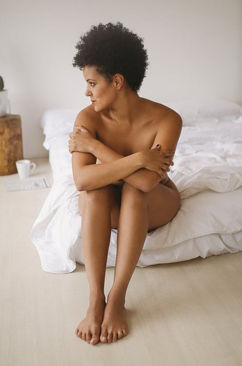 Naked woman sitting on bed in bedroom