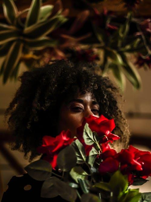 Woman Behind Red Flowers