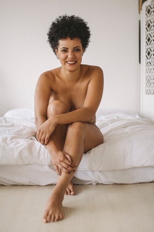 Naked ethnic woman sitting on bed in bedroom on sunny morning