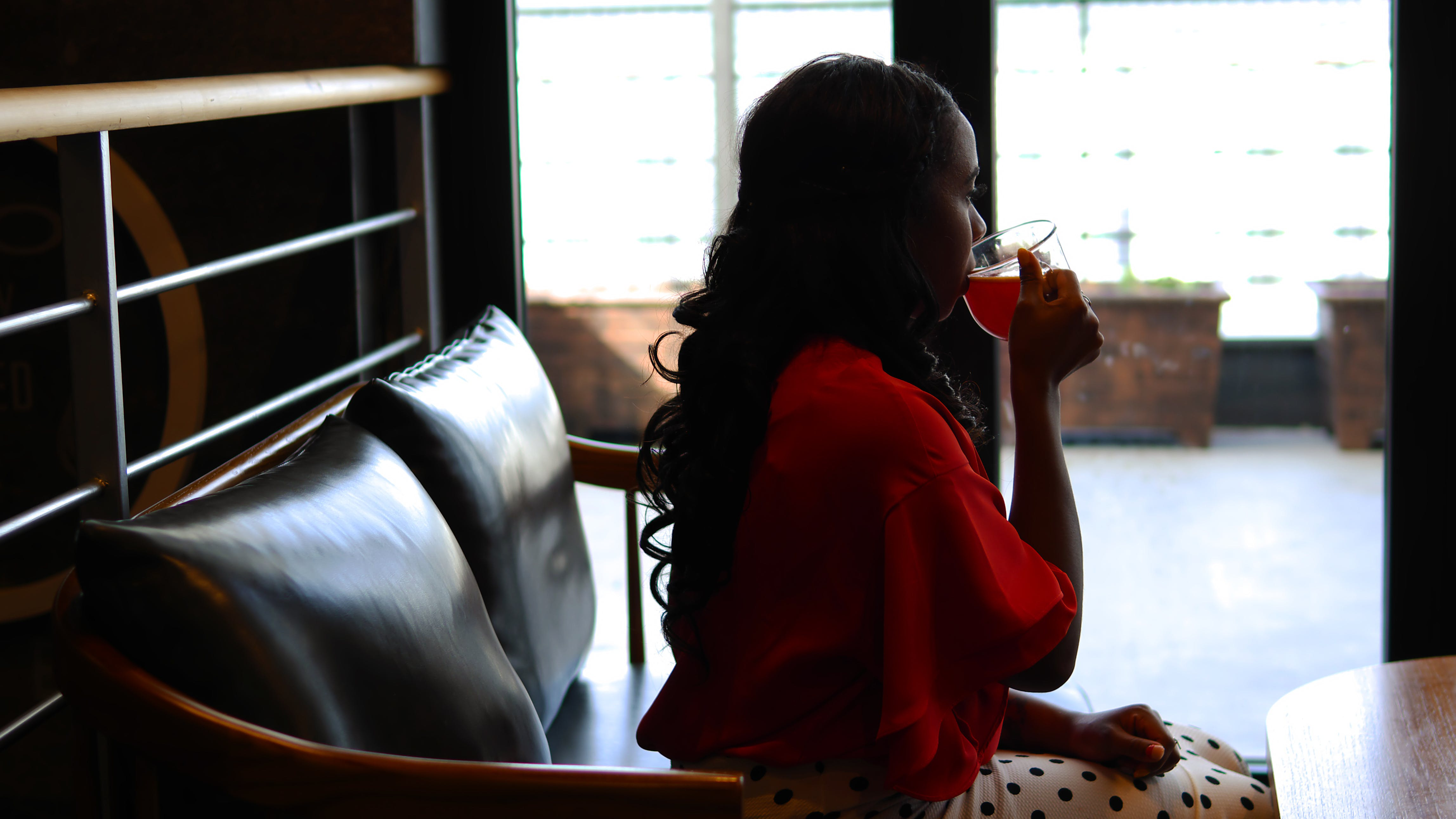 Woman Wearing Red Long-sleeved Blouse Sitting and Drinking Liquid