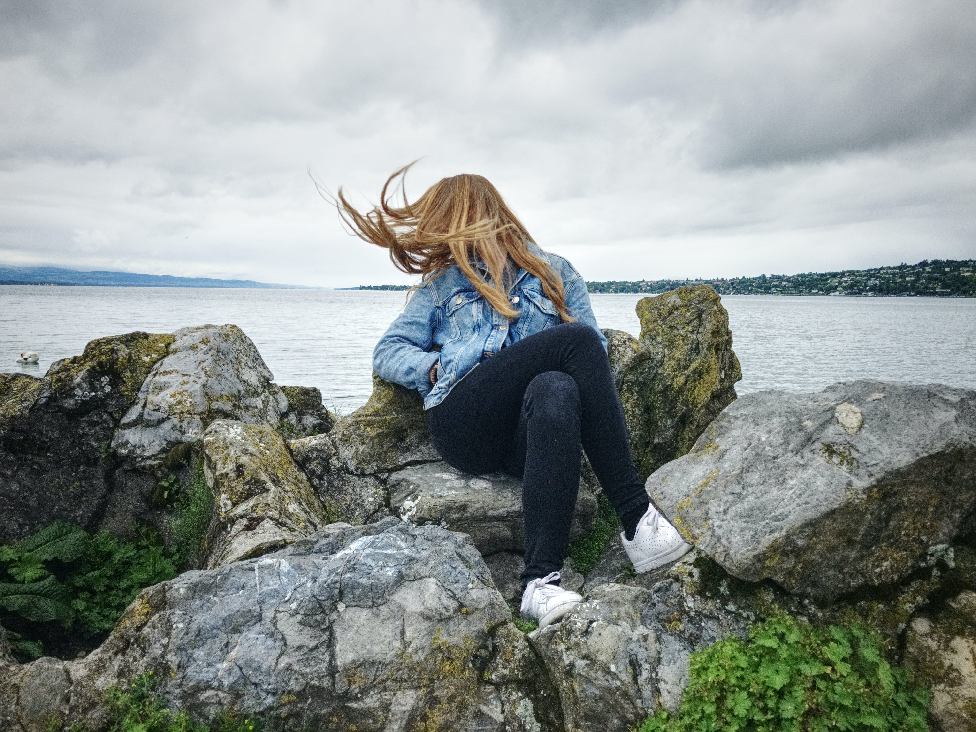 Woman With Blue Denim Collared Button-up Jacket and Black Jeans Sitting on Gray Rock Watching Lakeview