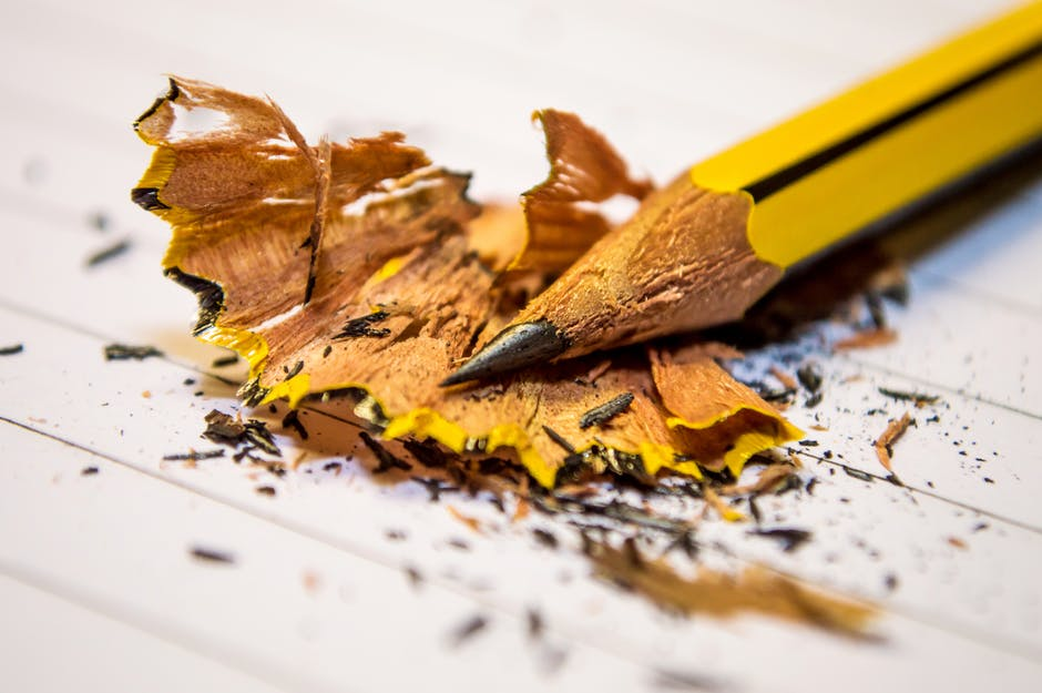 Yellow Black Pencil Sharpened Above the White Paper in Macro Photography