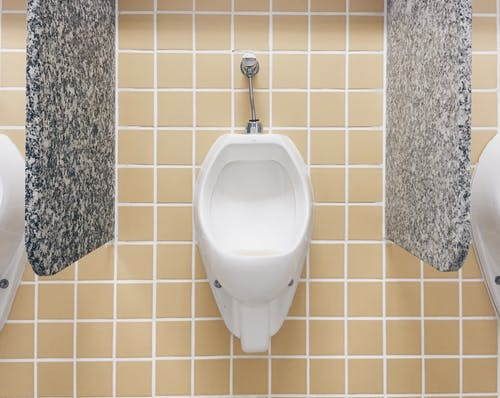 White Ceramic Urinal Toilet Mounted on Tiled Wall