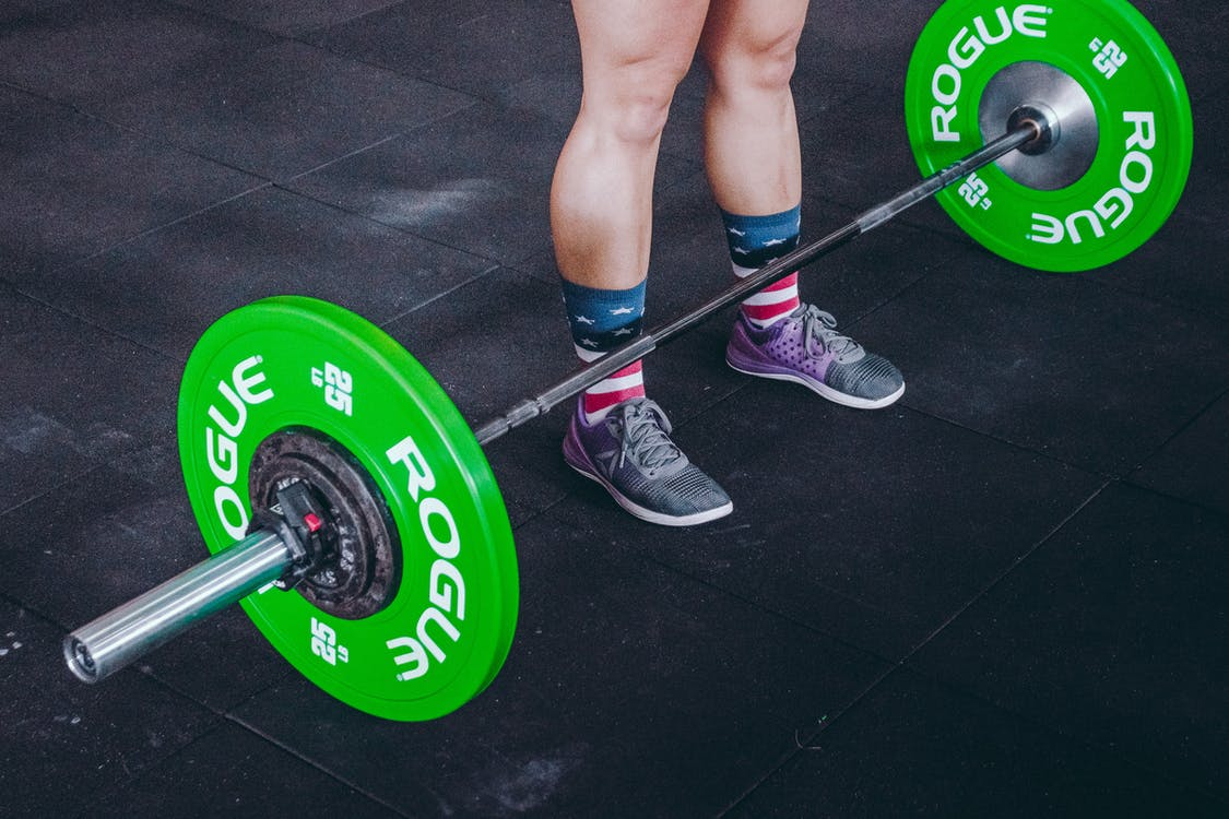 Person Standing in Front of Green and Gray Barbell