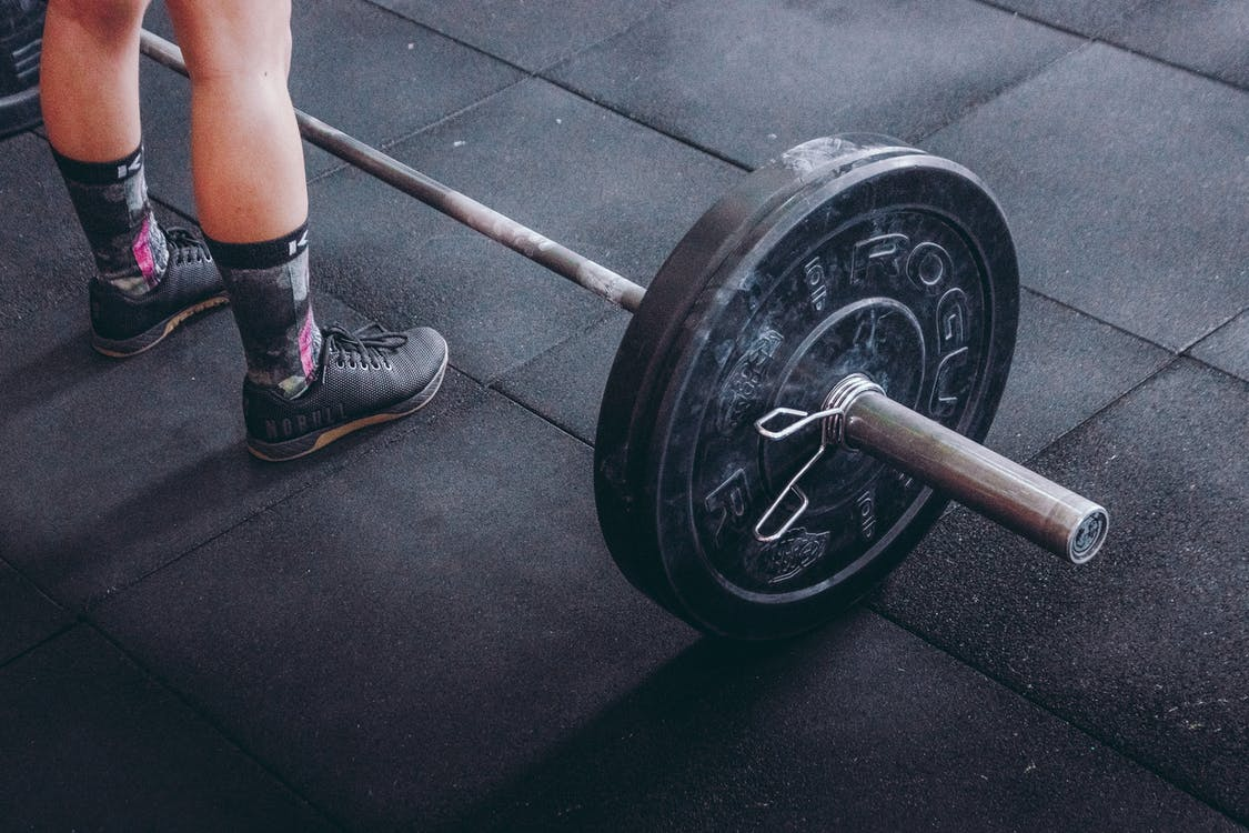 Person Standing Near Black Barbell