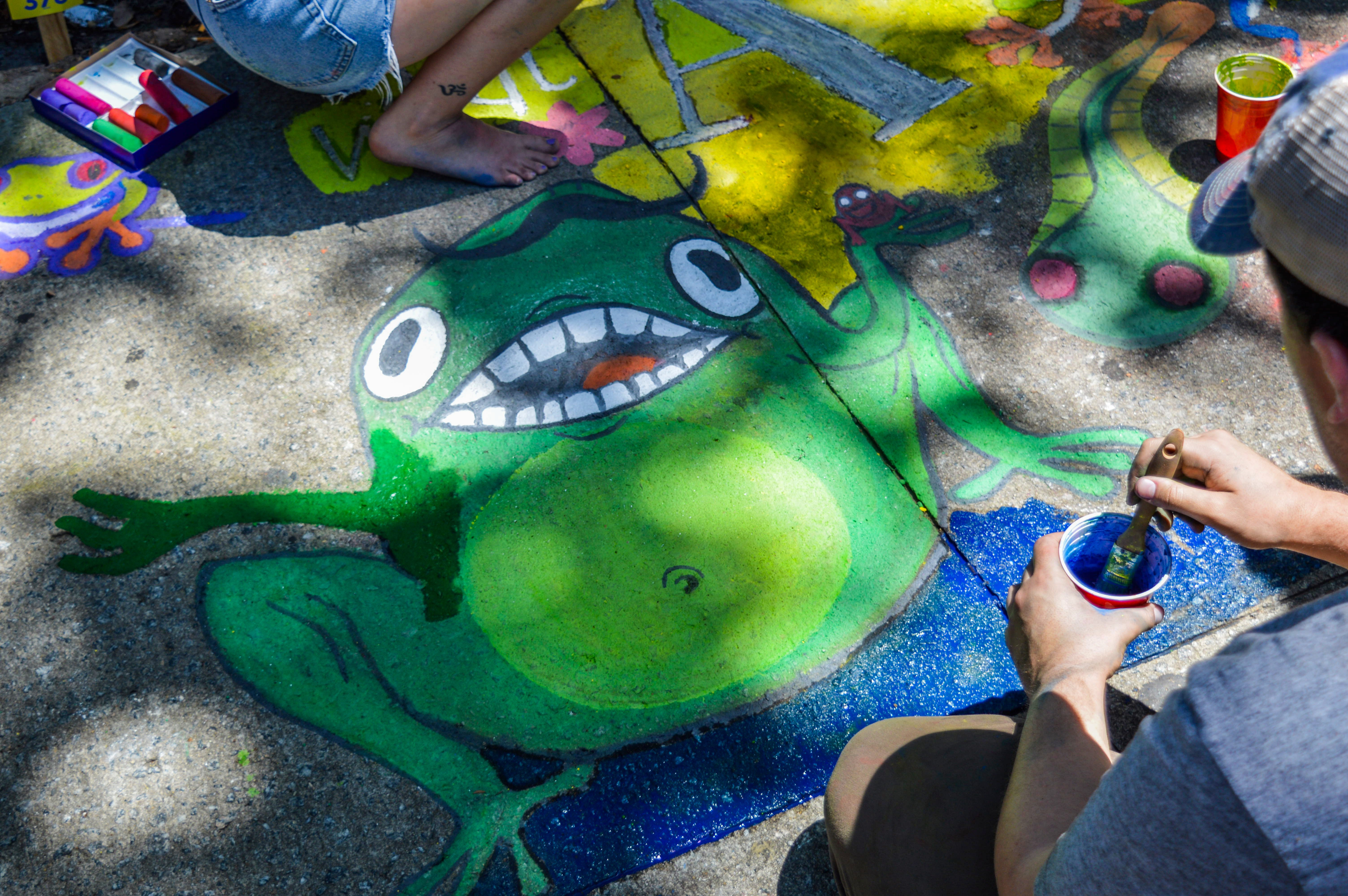 Man Painting Green Frog On Ground