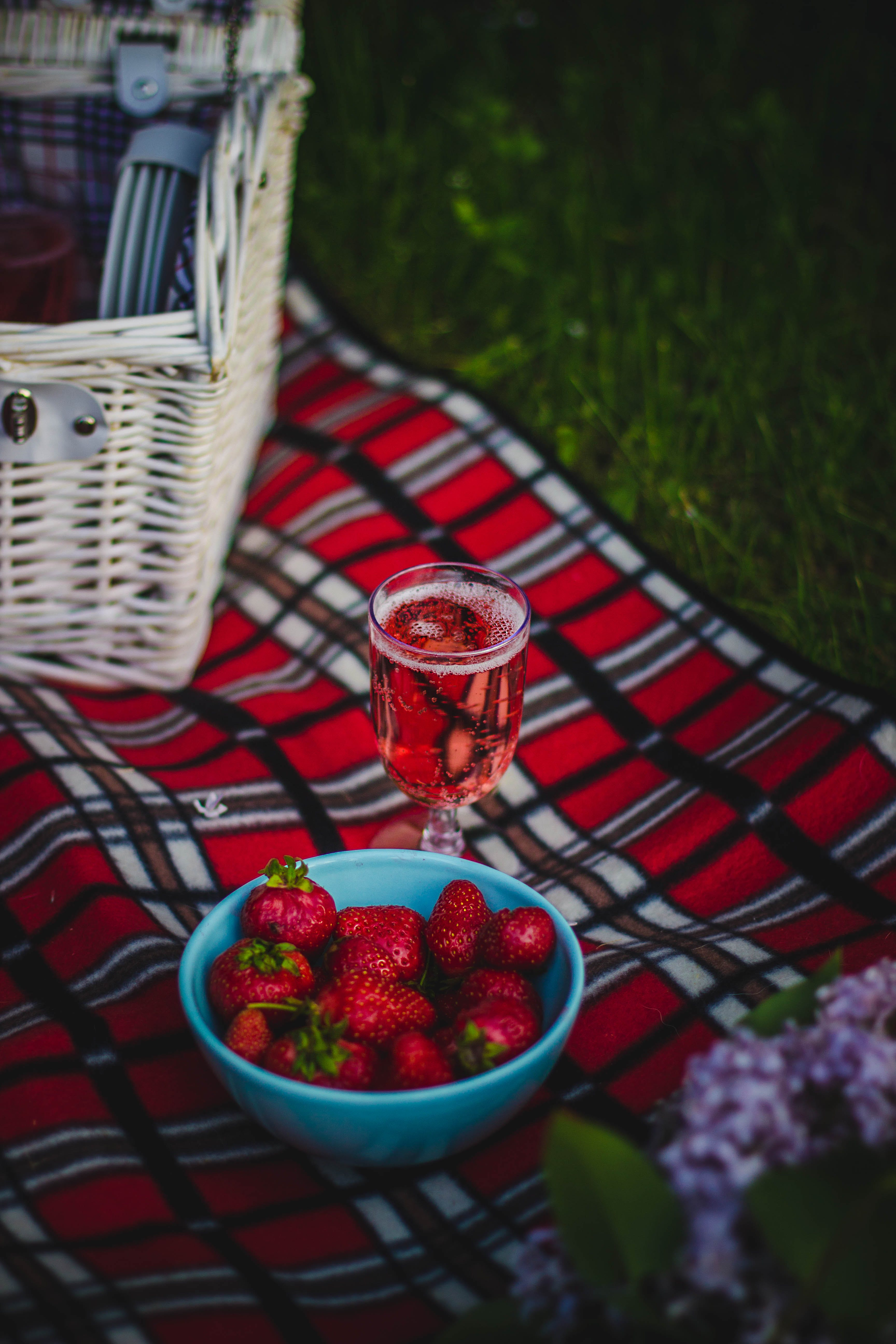 Clear Wine Glass With Wine Near Strawberry Fruit on Red White and Black Plaid Textile
