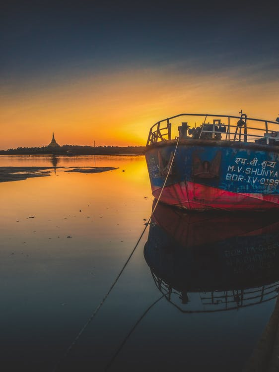 Blue and Red Ship during Golden Hour