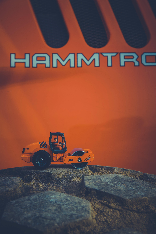 Orange and Black Road Roller Toy on Black Stone