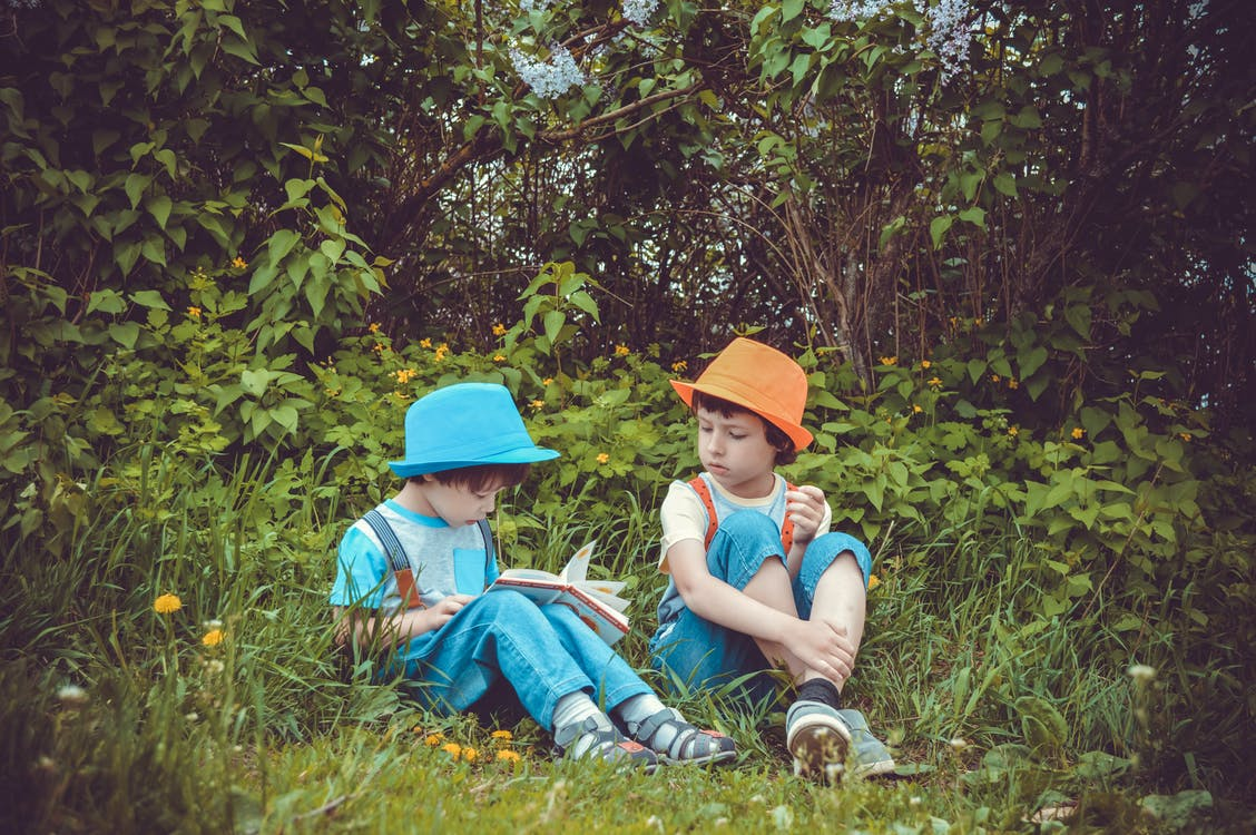 Girl and Boy Sitting on Grass Field Surrounded by Trees