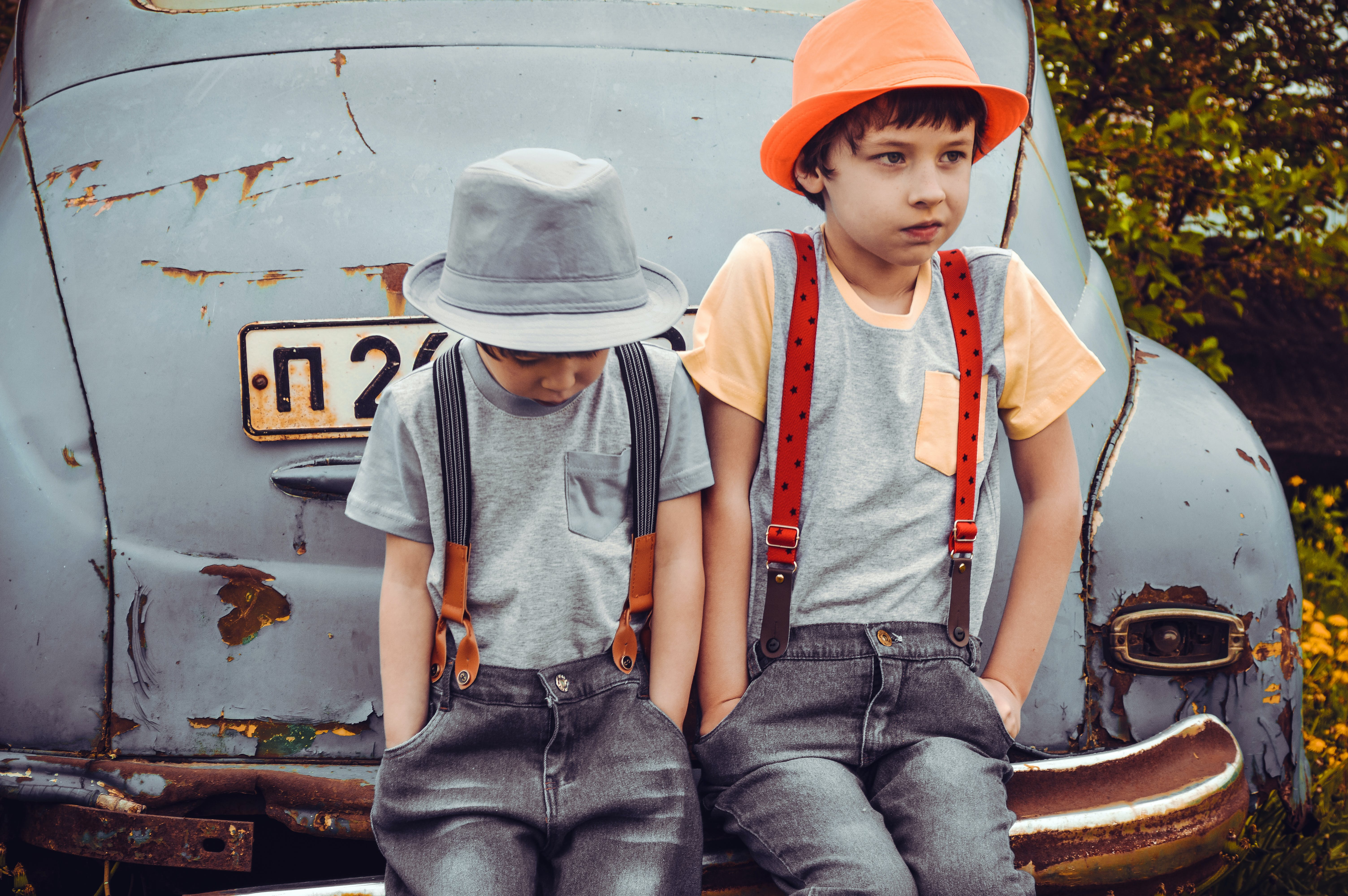Two Boys Wearing Gray Shirts Sitting on Gray Vehicle Bumper