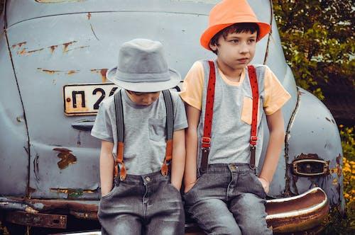 Two Boys Wearing Gray Shirts Sitting on Gray Vehicle Bumper