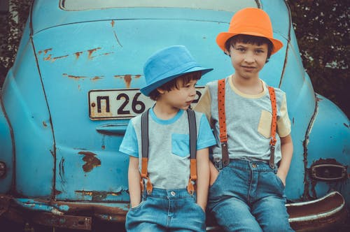 Two Boys Sitting on Blue Volkswagen Beetle Coupe's Rear Bumper