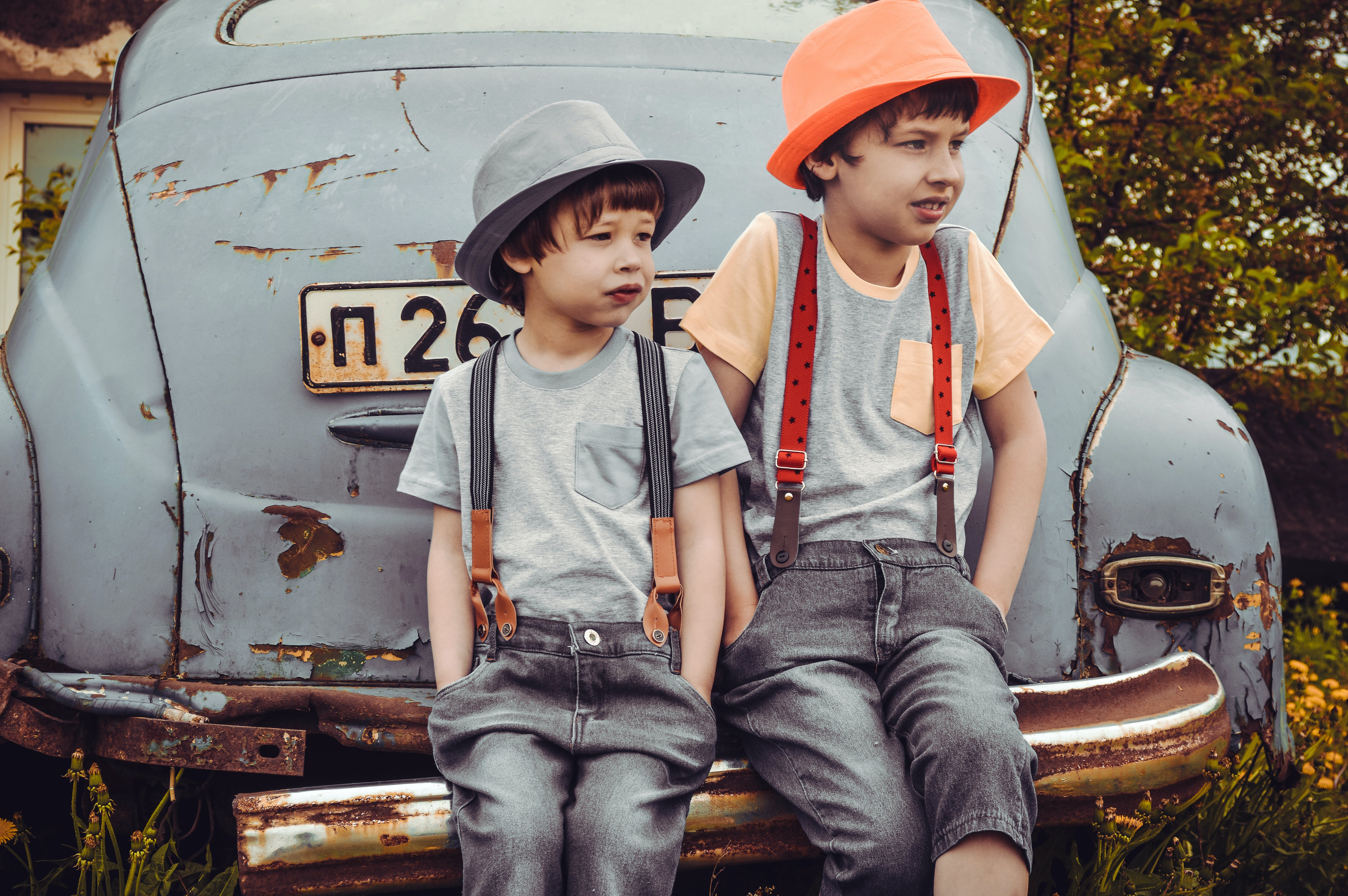 Two Boys Sitting on Vehicle Bumper