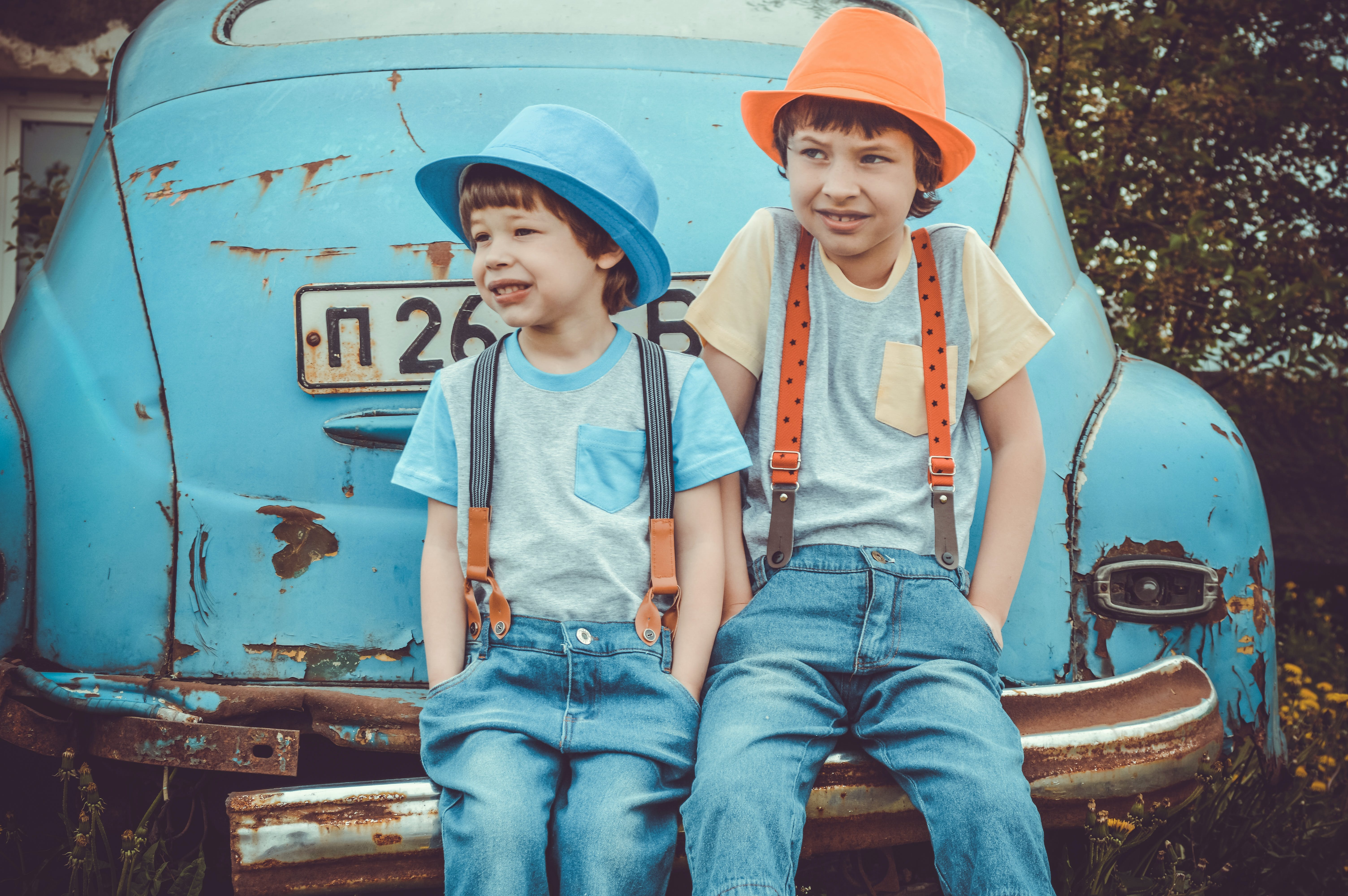 Two Boys Sitting on Classic Blue Car's Rear Bumper