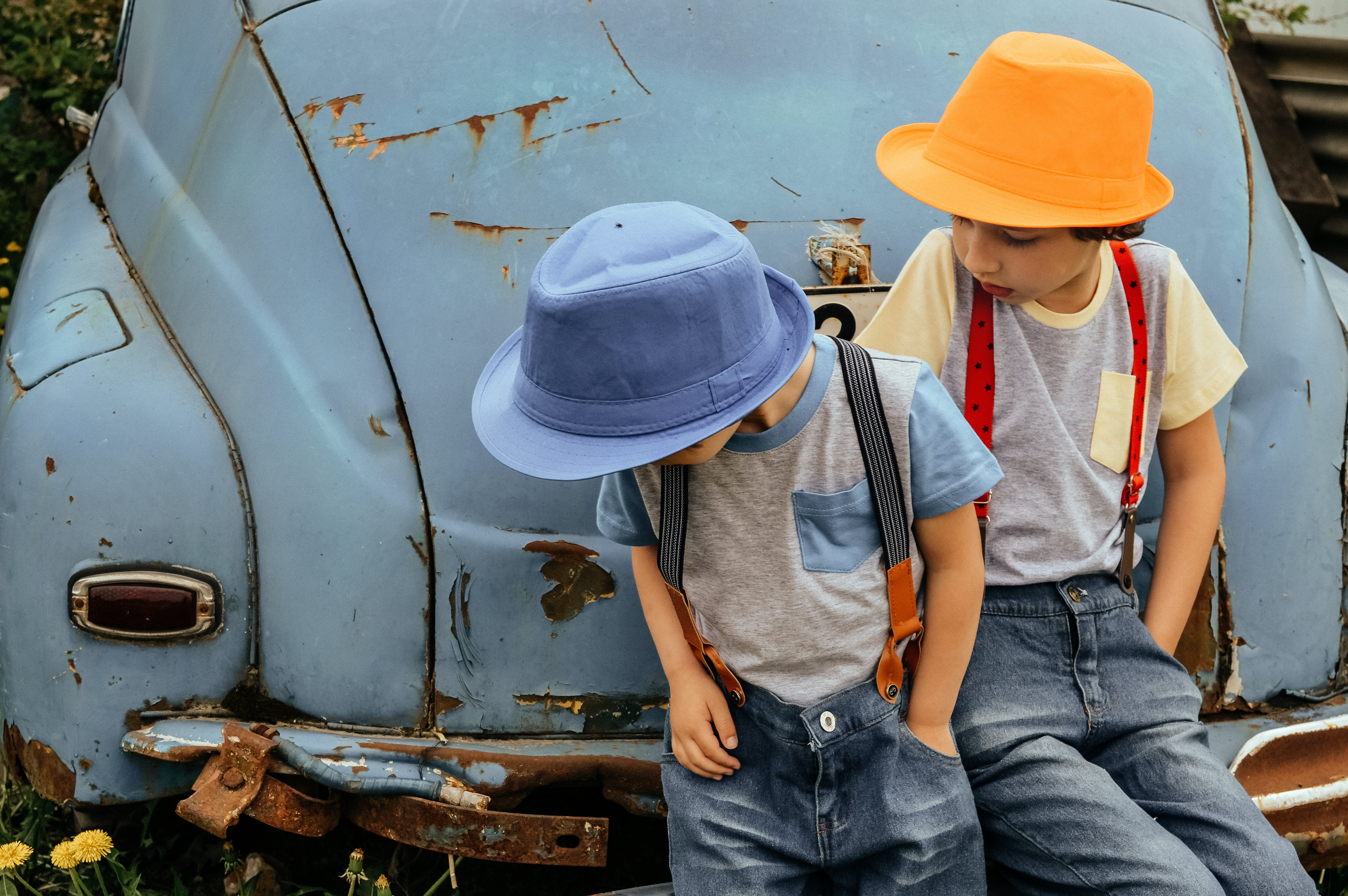 Two Boy in Grey Shirts and Blue Overall Pants Sitting on Blue Car Bumper