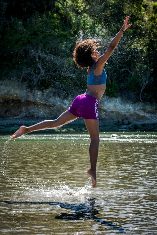 Woman in Blue Sports Bra and Purple Shorts Leaping Above Body of Water