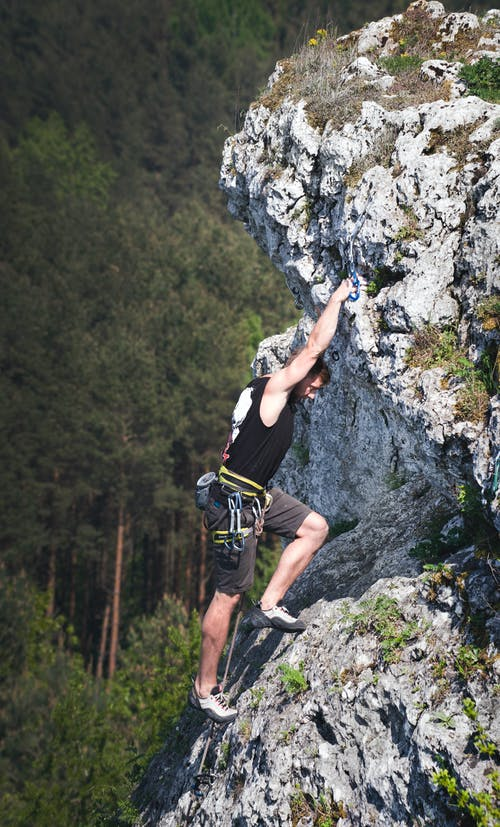 Man Wearing Black Tank Top and Brown Shorts Climbing Rock