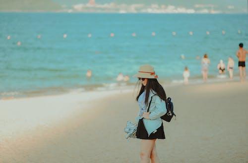 Girl in Cyan Jacket Walking on Beach