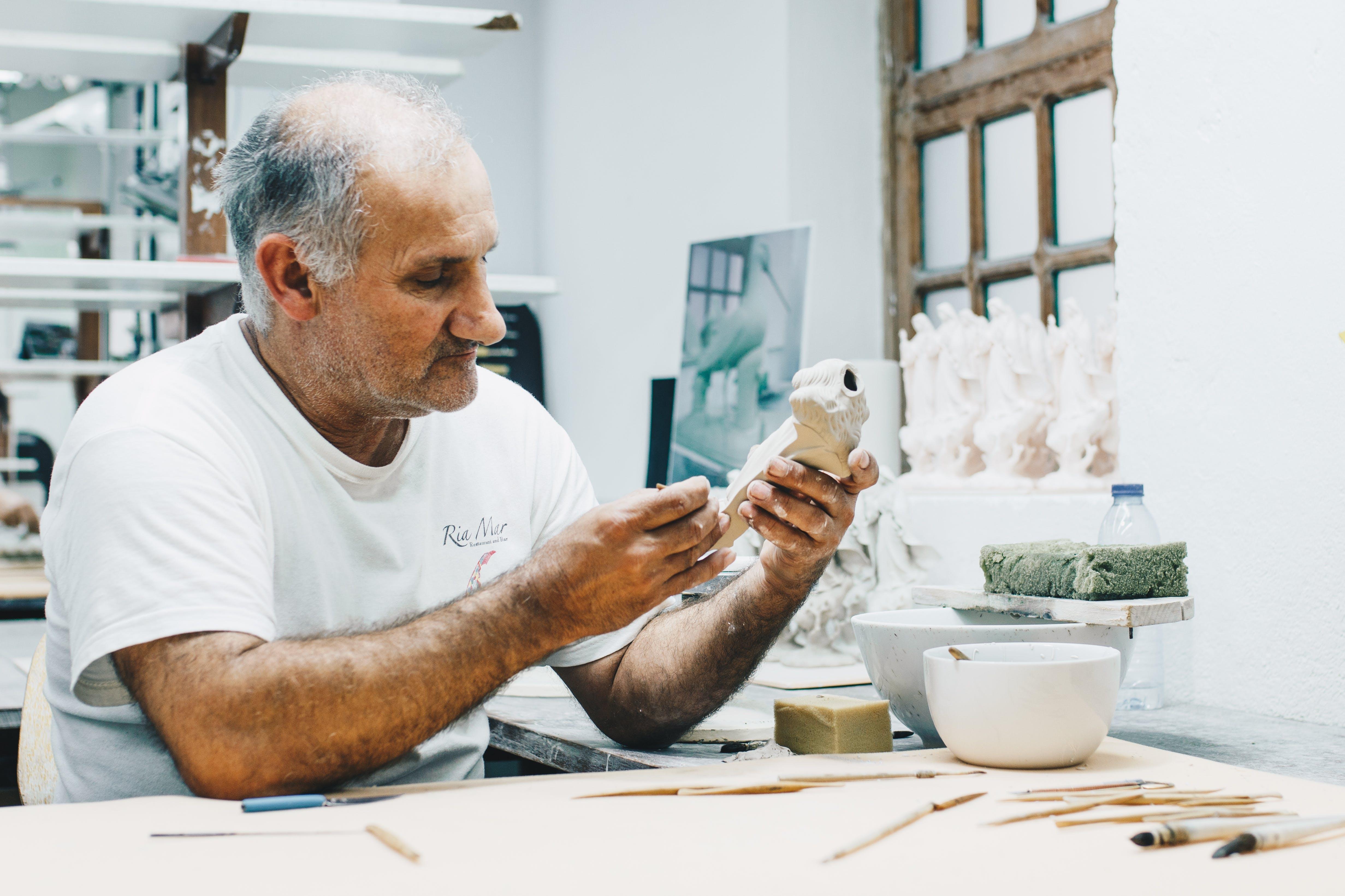 Man in White Crew-neck T-shirt Holding White Figurine