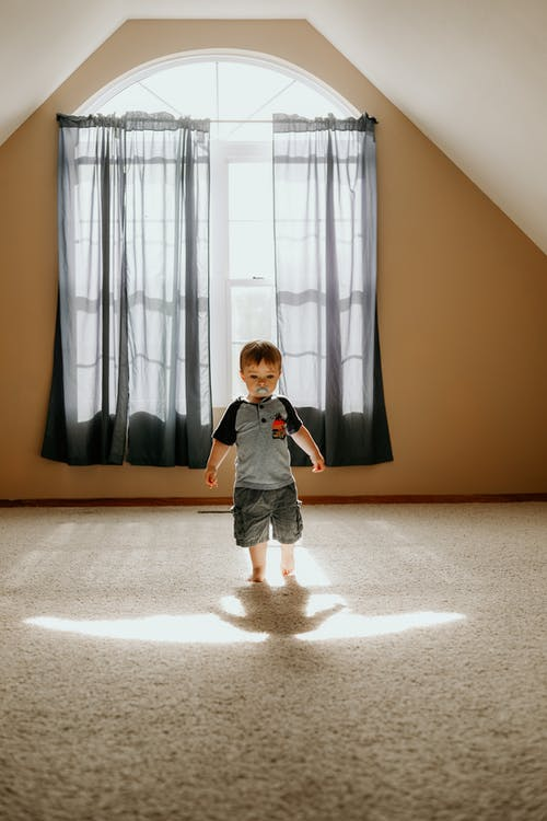 Boy Wearing Gray T-shirt and Gray Cargo Shorts Inside White Painted Wall Room