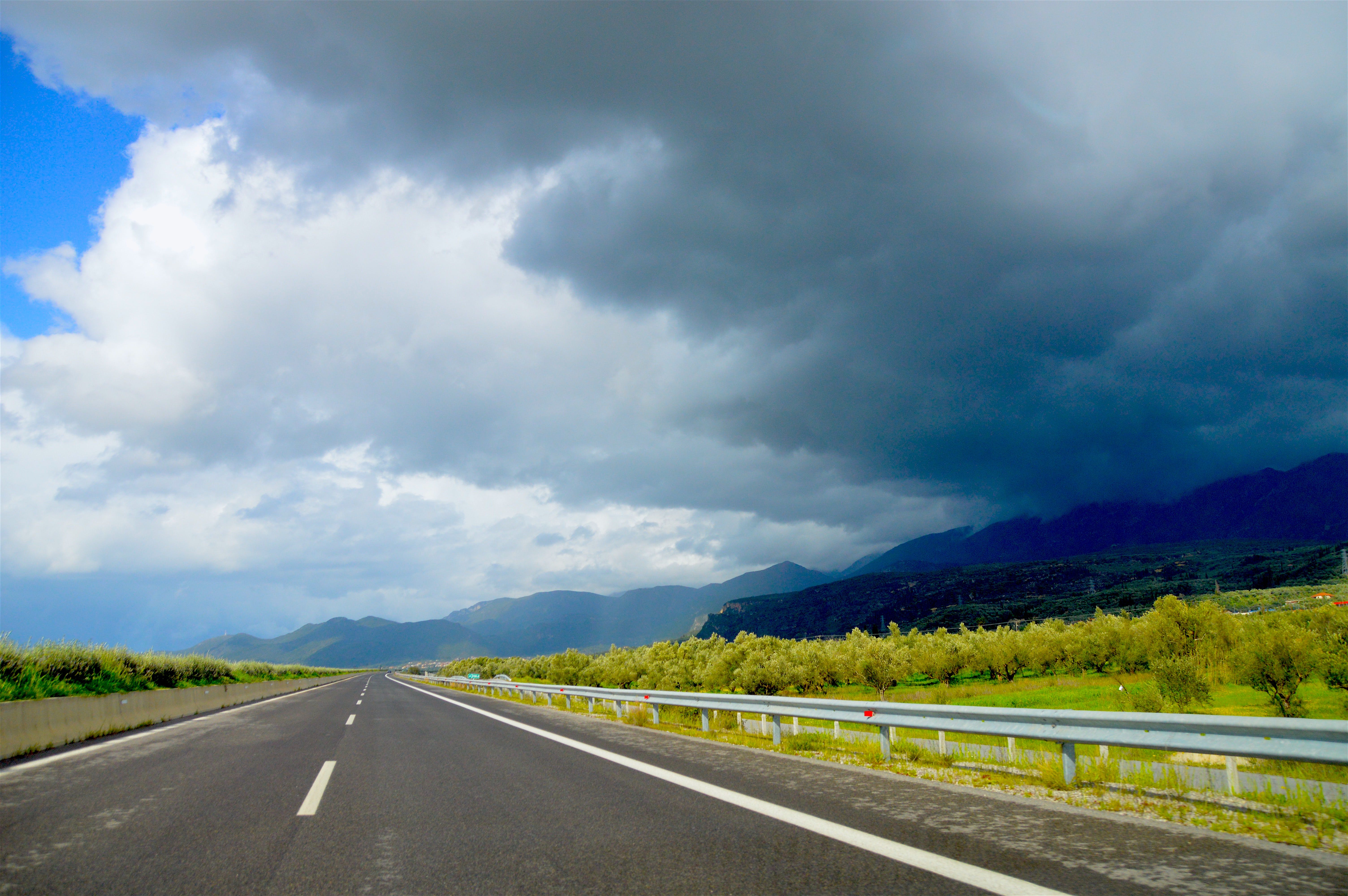 Photo of Road Near Green Leaf Trees Under Dark Clouds at Daytime