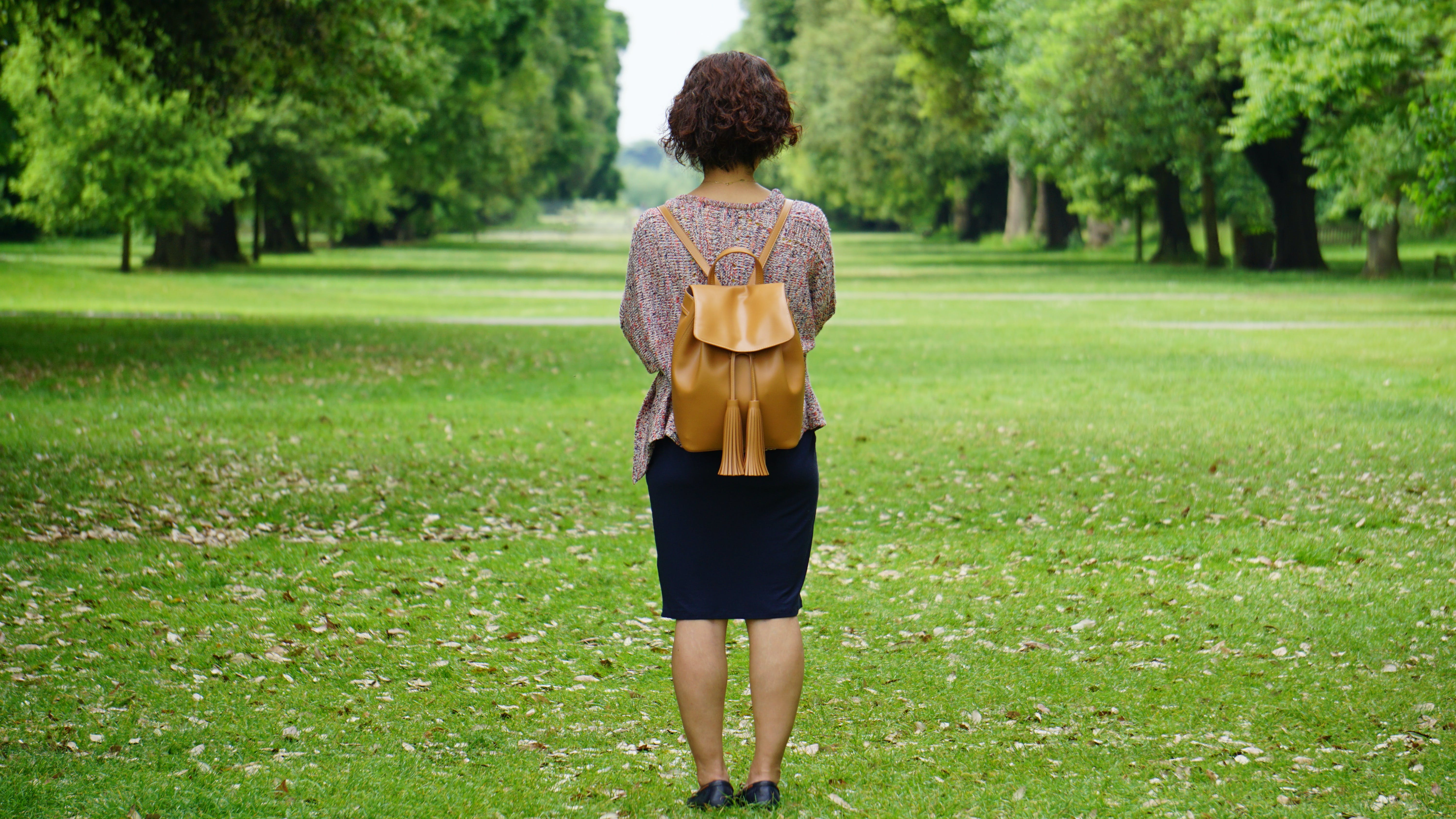 Woman Standing on Green Grass Lawn