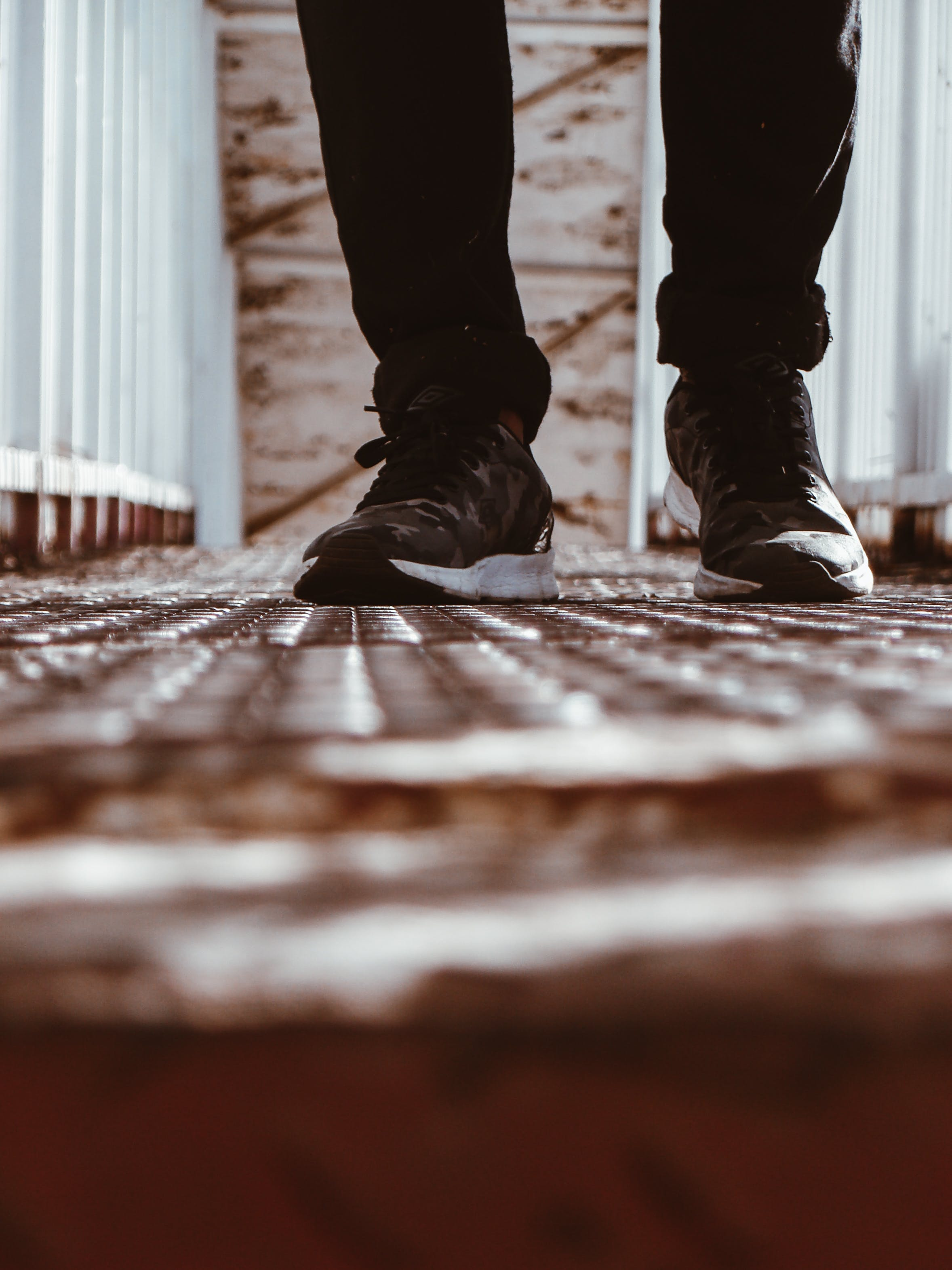 Person in Black-and-white Shoes Standing on Brown Metal Floor