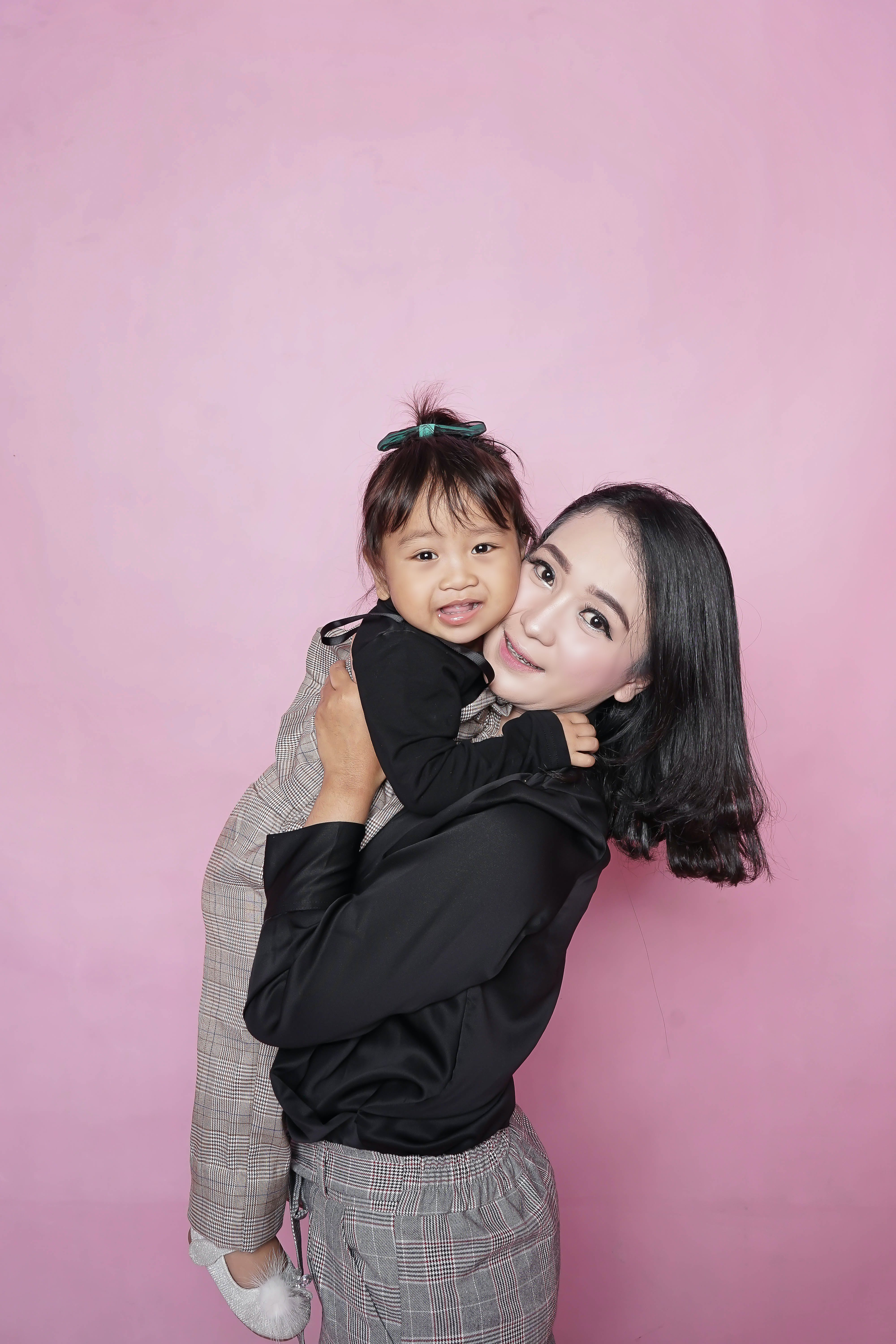 Woman Holding Toddler Girl Against Pink Wall
