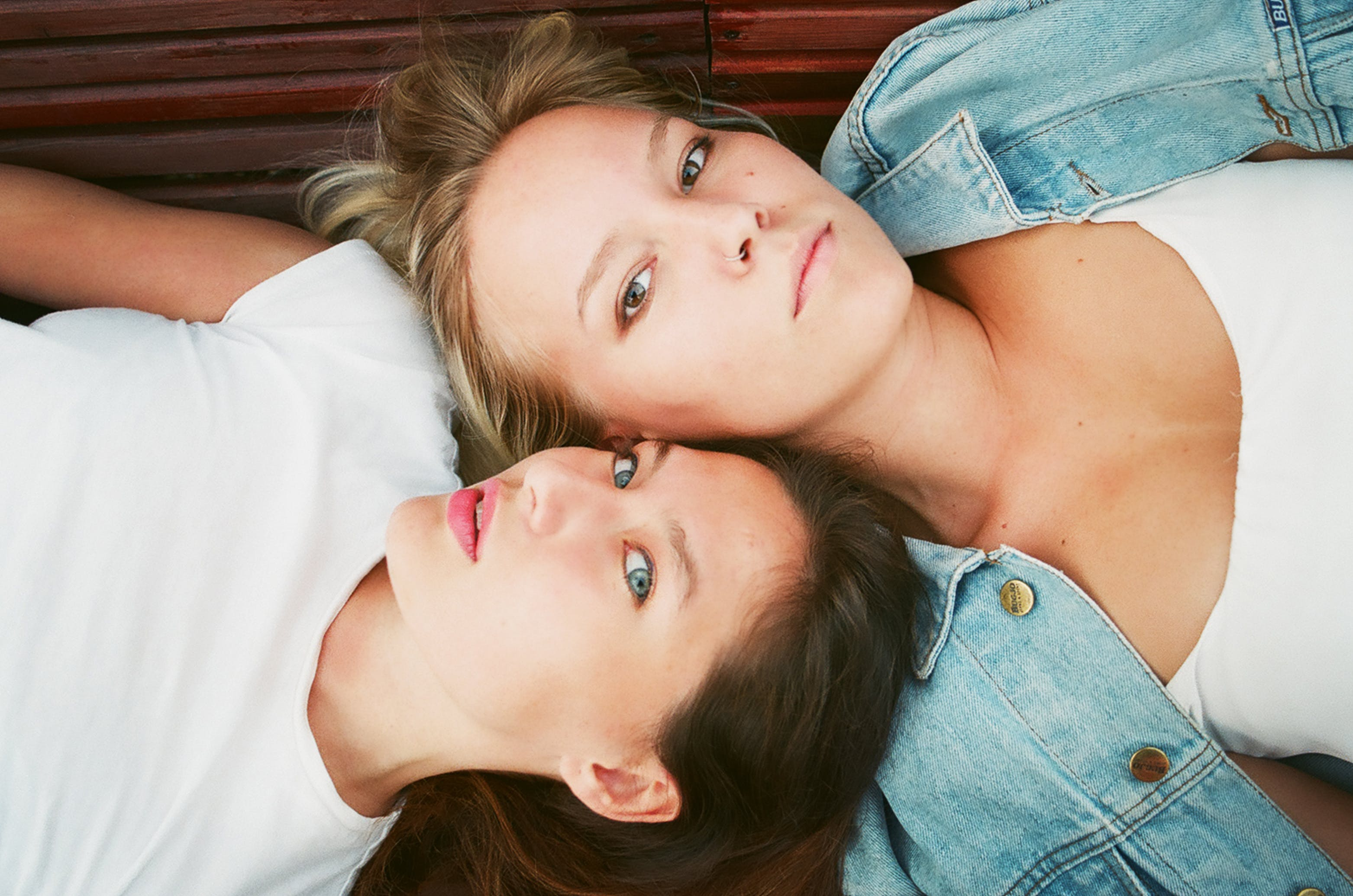 Two Woman Lying on Brown Surface in High Angle Photo