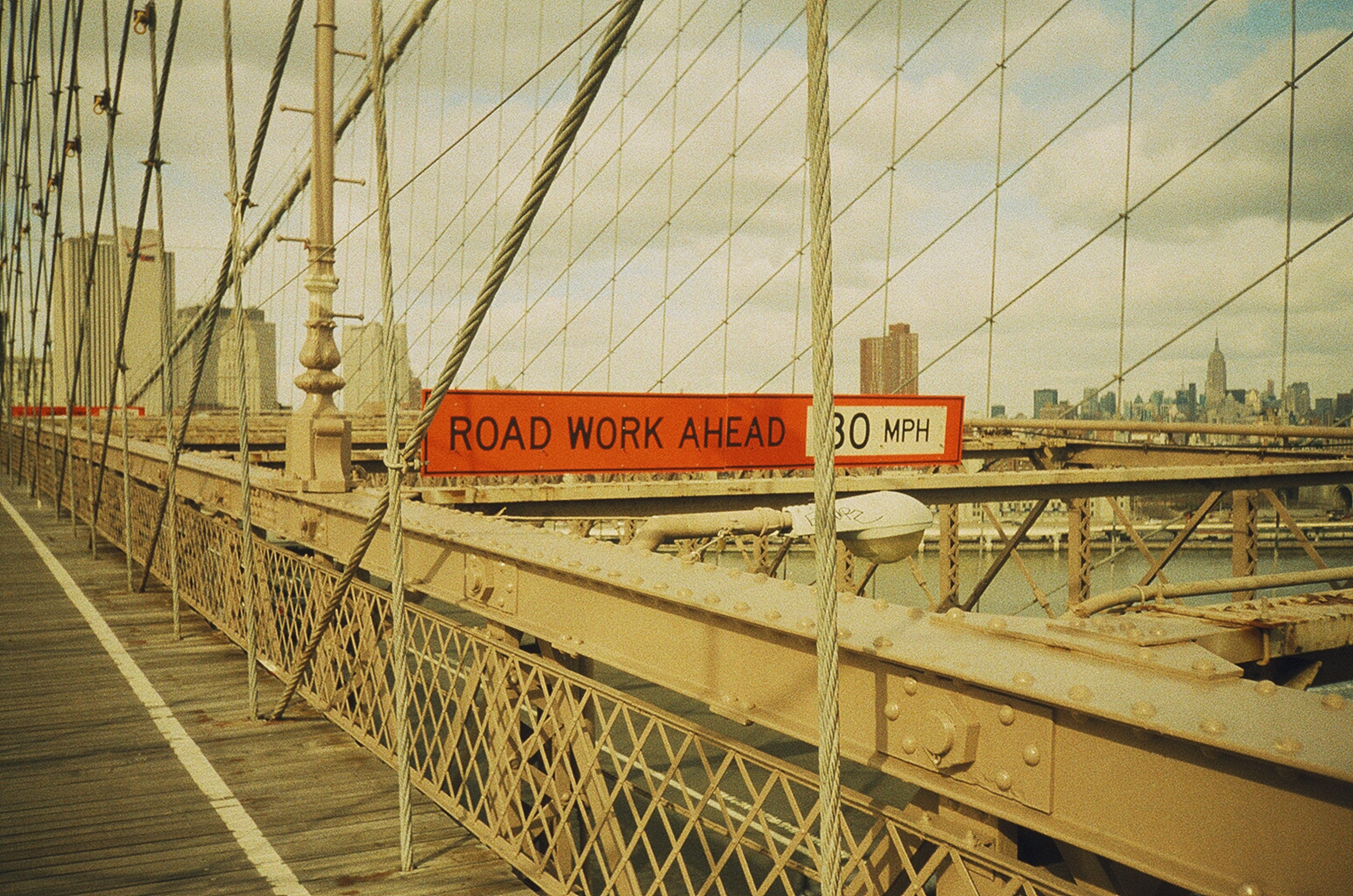 Red and White Signage With Road Work Ahead Text