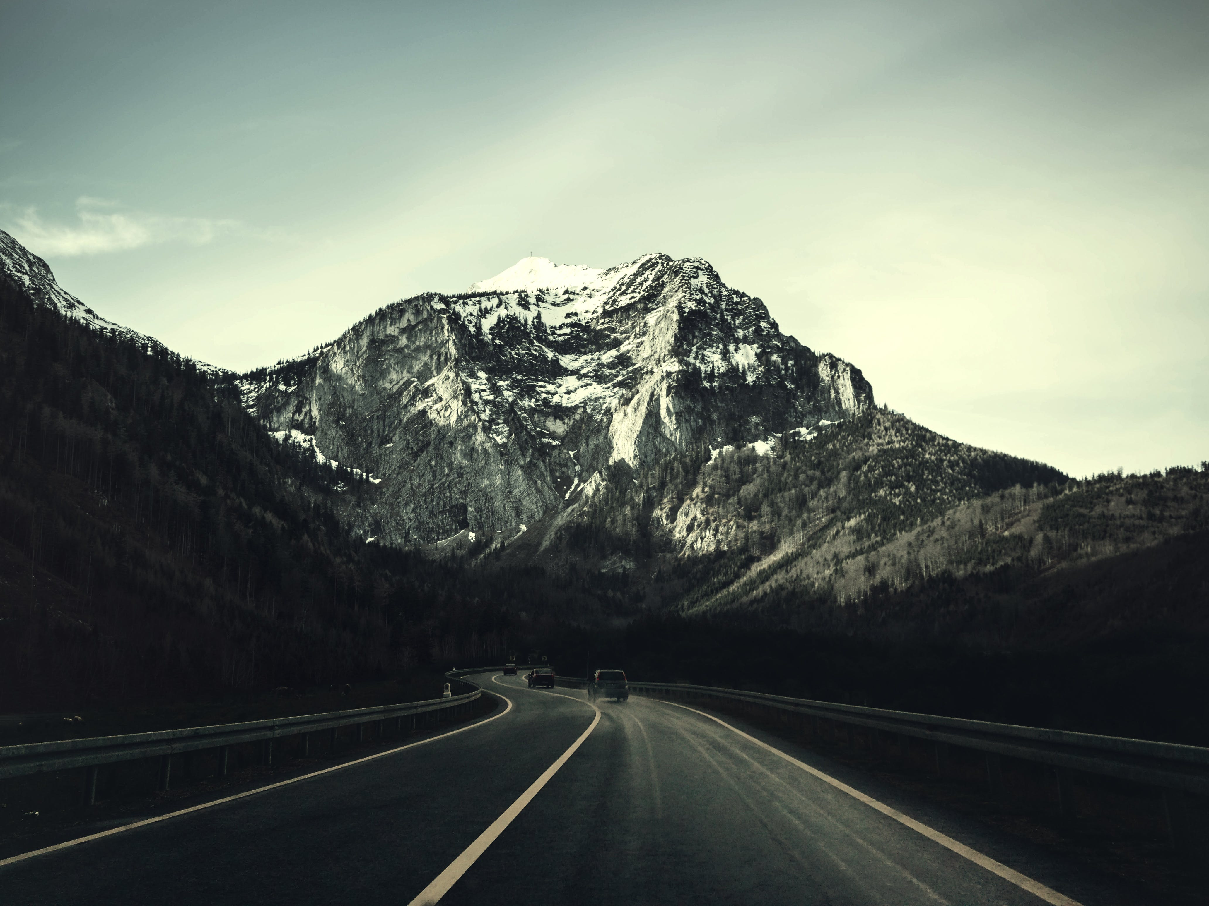 Asphalt Road With Running Vehicle Infront of Mountain Under Gray Sky