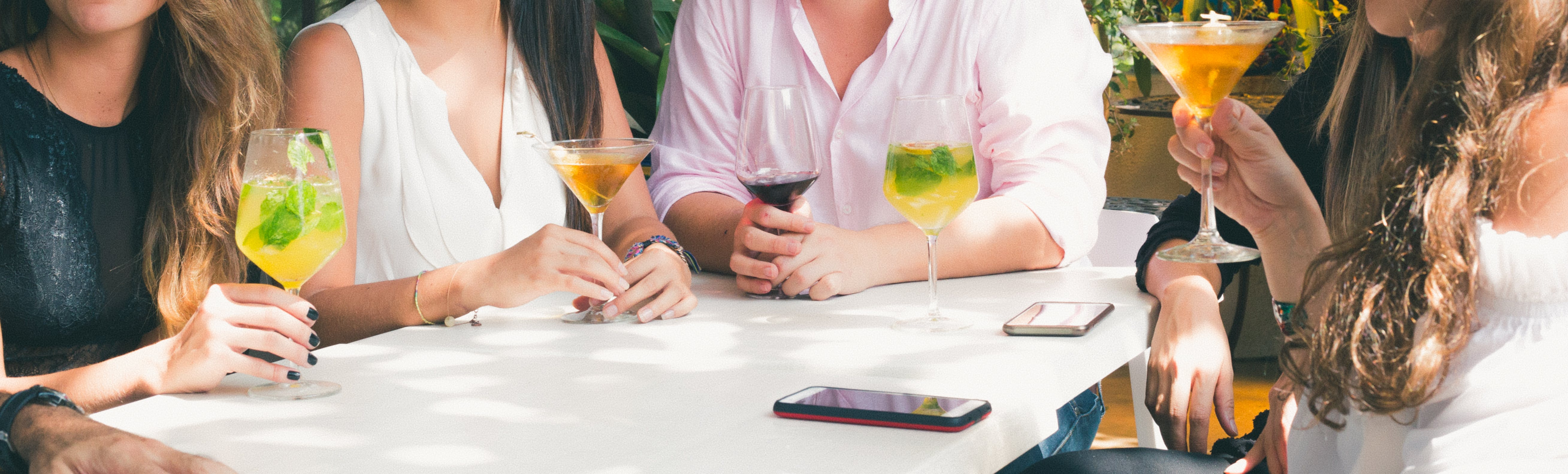 People Drinking Beverage While Sitting Near Table