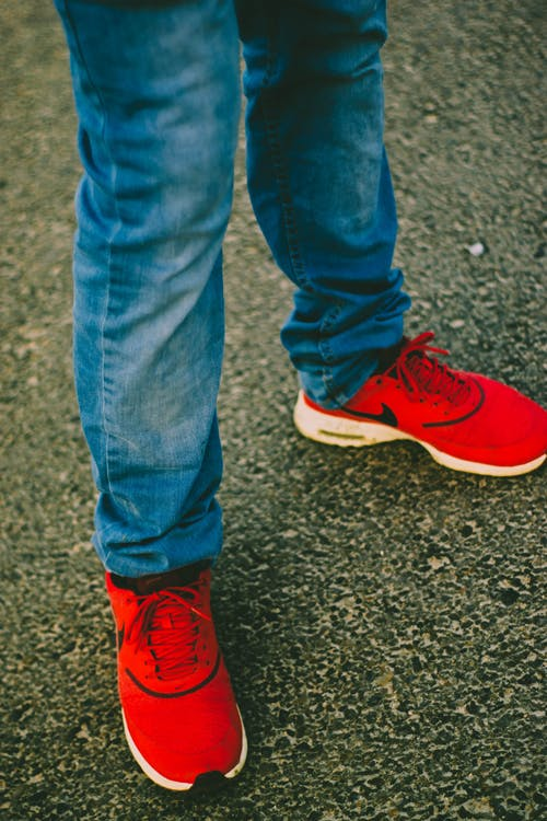 Person Wearing Red Nike Running Shoes