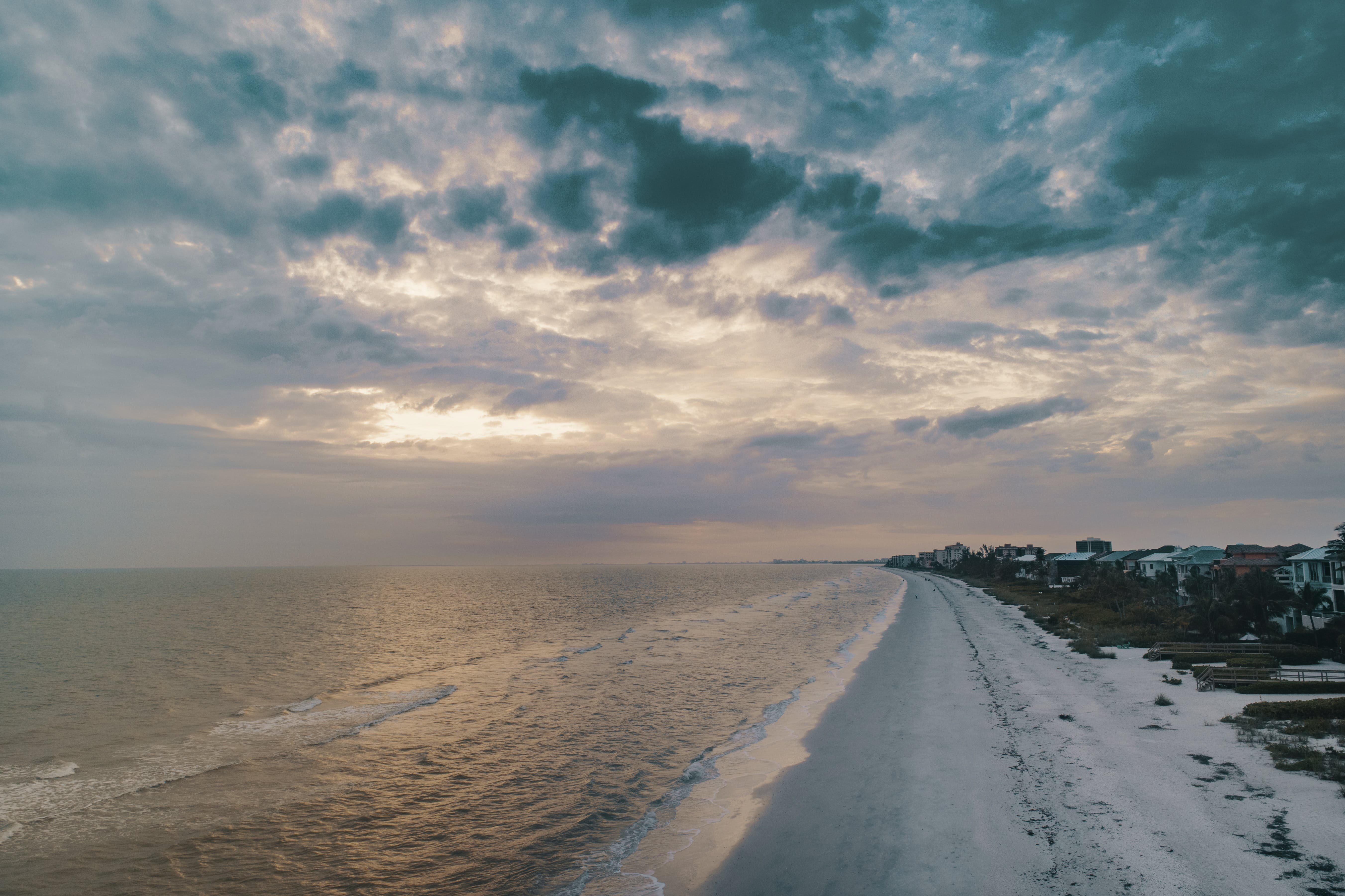 Wide Angle Photo of Shore Under Cloudy Sky