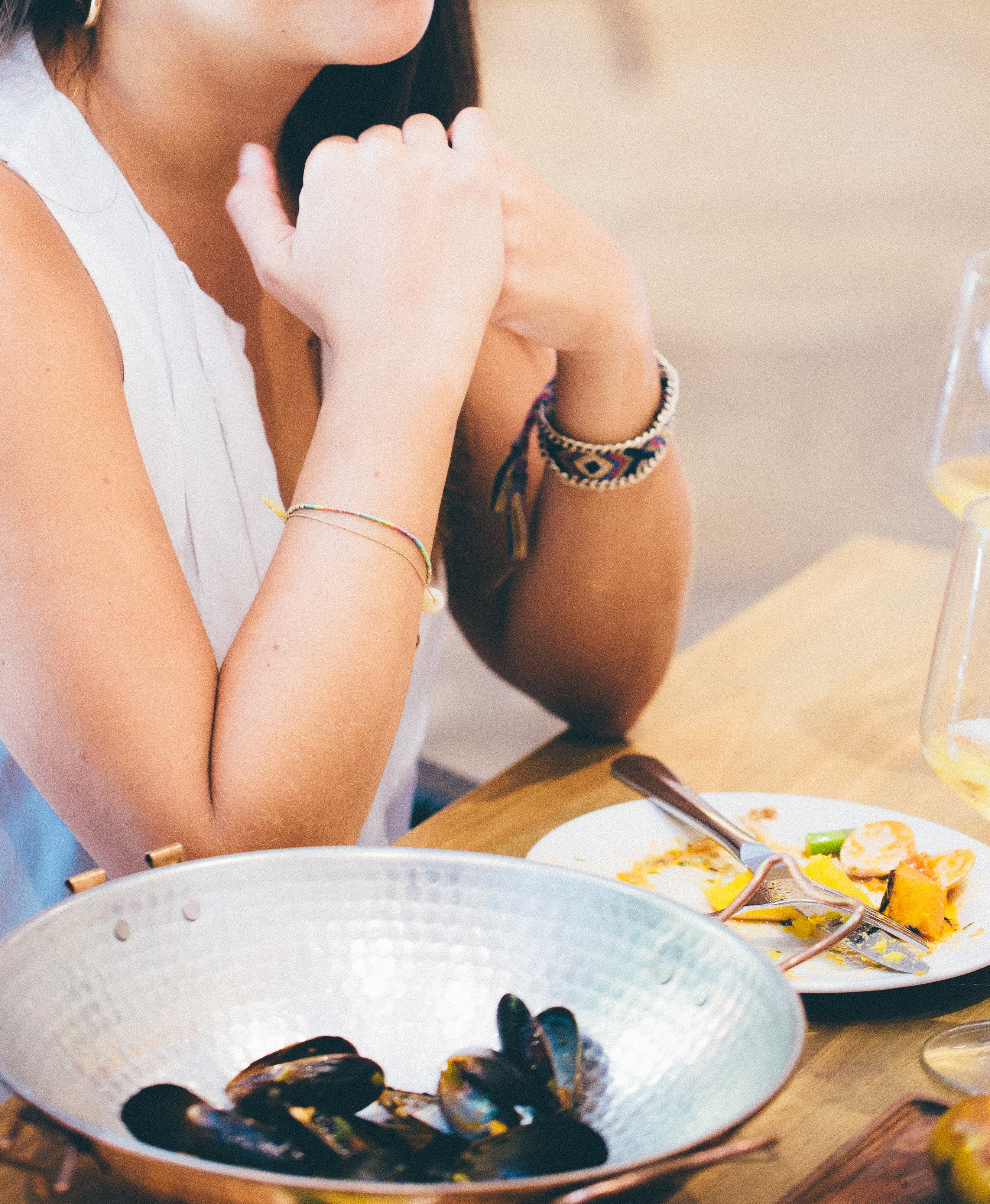 Woman Wearing White Deep V-neck Sleeveless Top Sitting on Chair Near Table